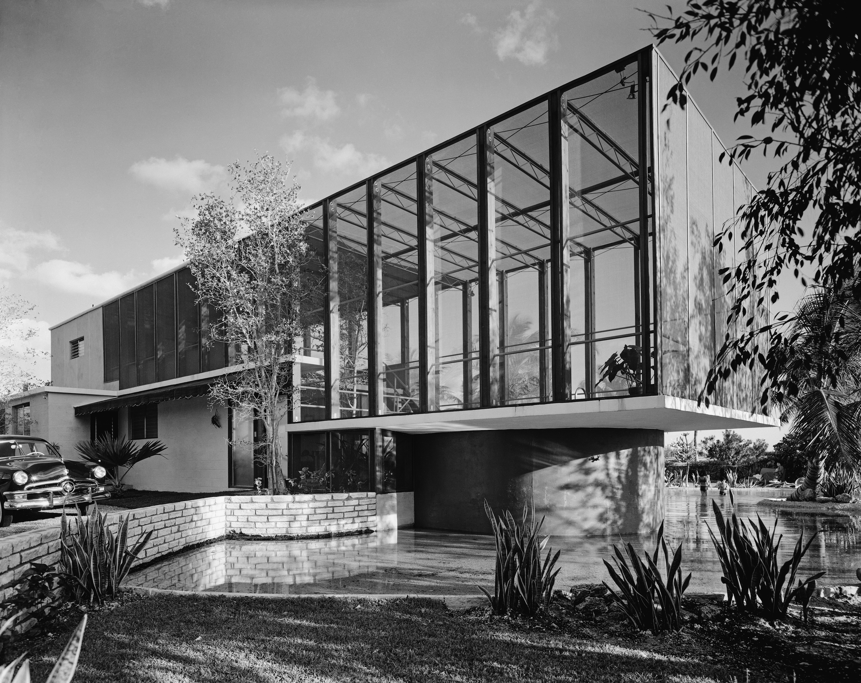 Black and white photograph showing a modern building with large glass wall.