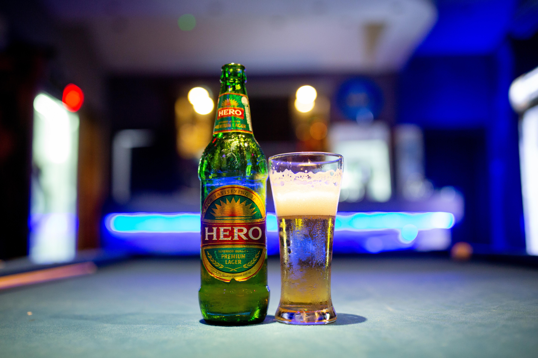 A bottle of Hero beer alongside a glass full of beer.