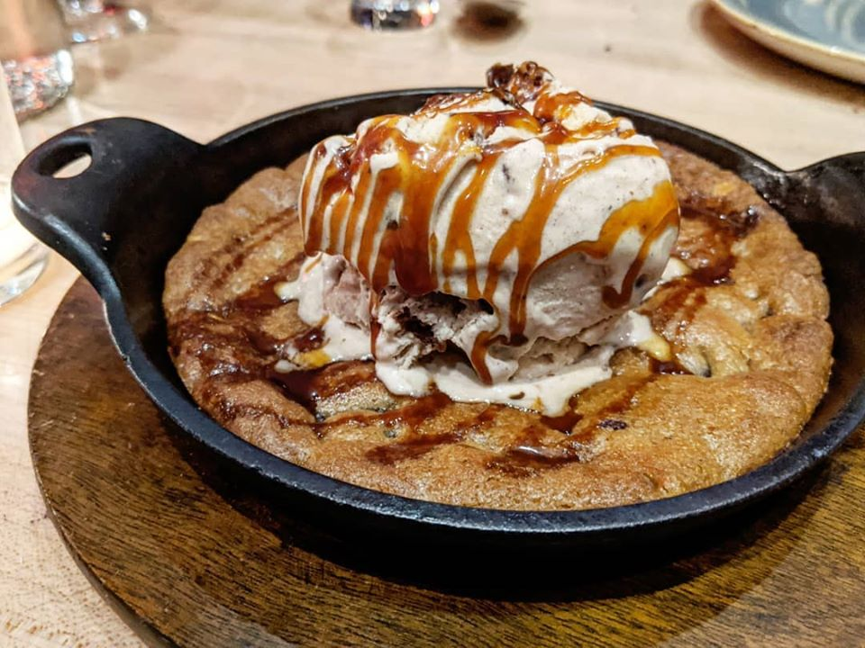 A cookie baked in a cast-iron skillet is topped with a scoop of ice cream and a drizzle of caramel