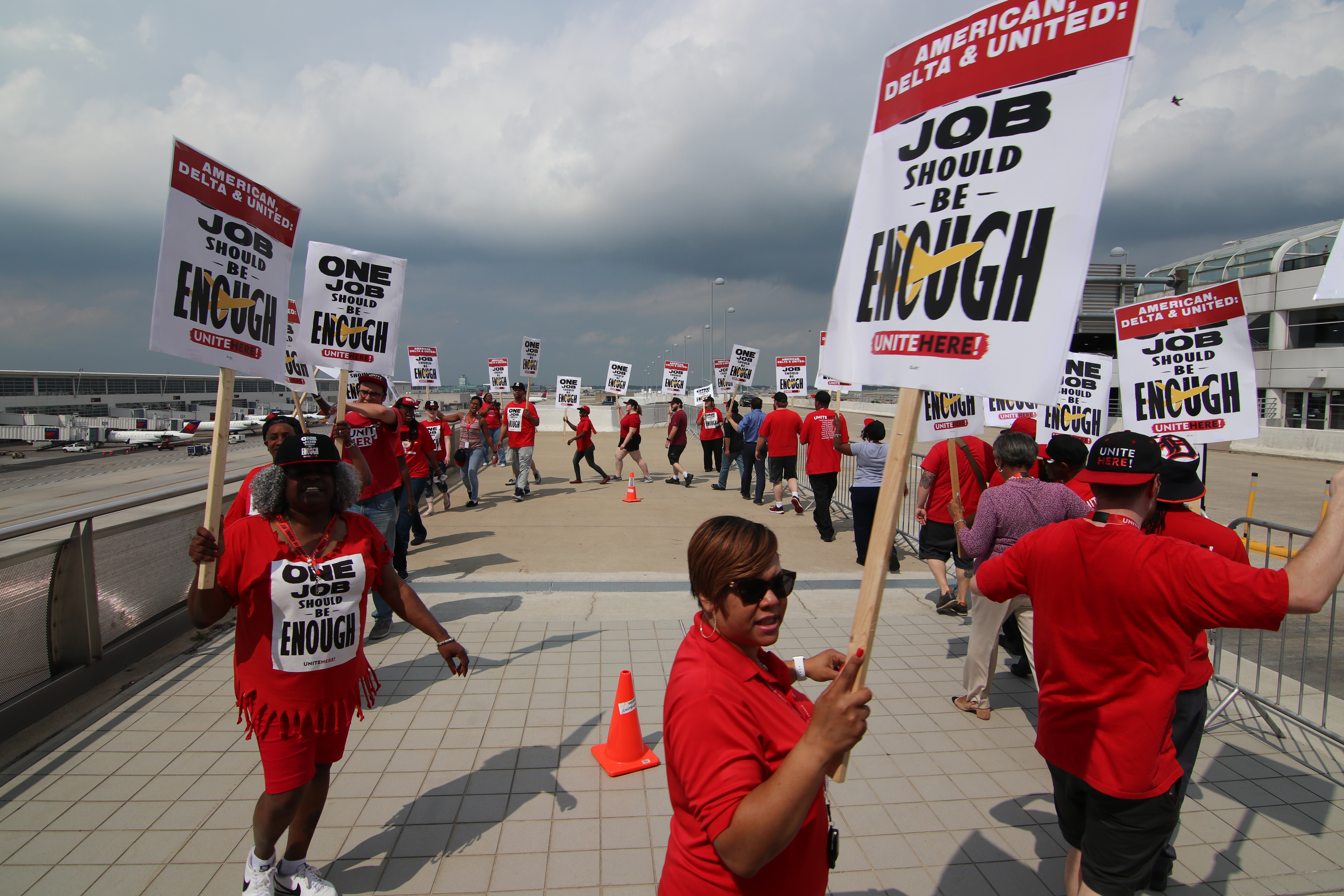 Airline catering workers in red shirts carry signs outside of DTW Airport in July.