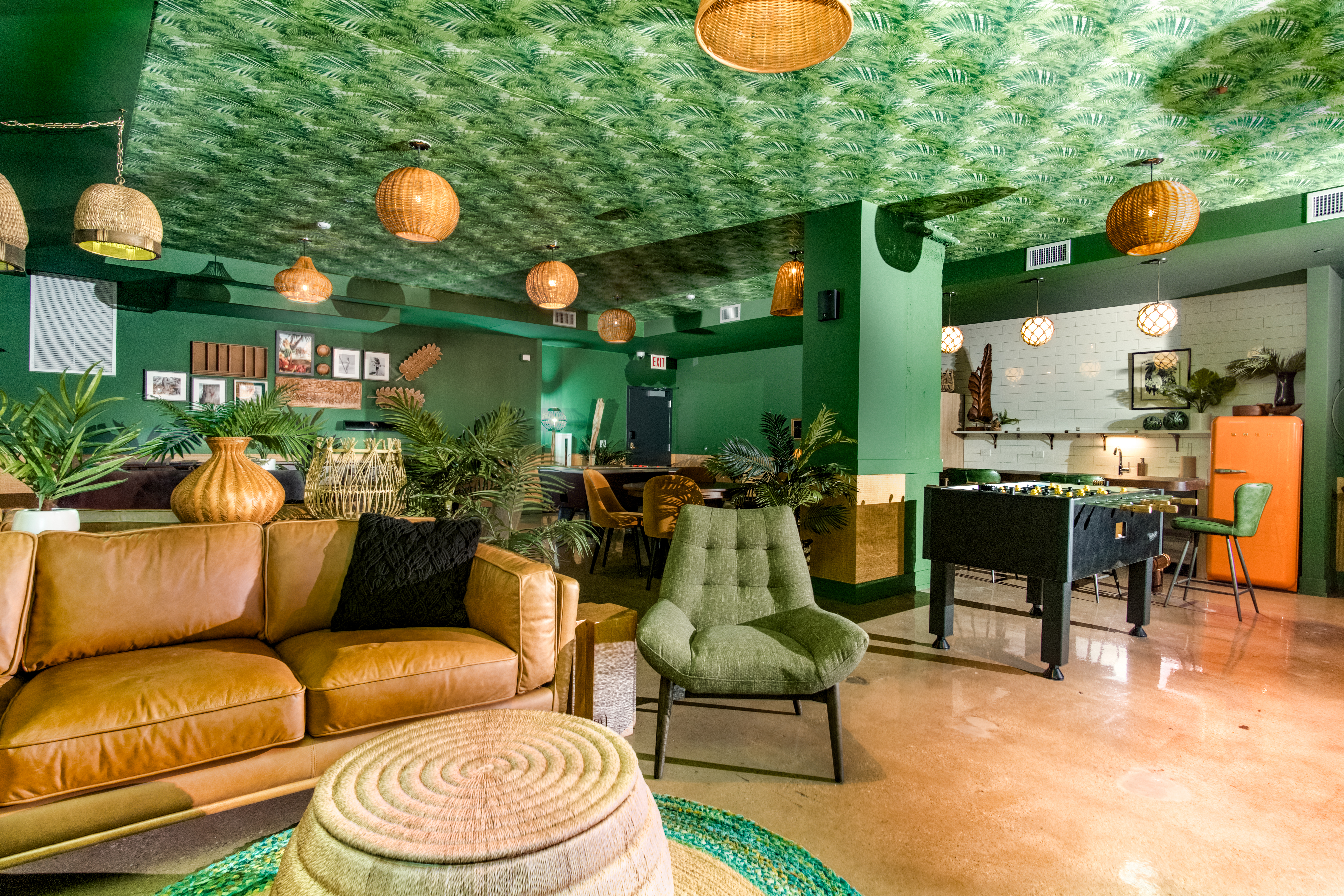 A lounge with a tropical theme including palm leaf patterned paper on the ceiling, wicker lamps, brown leather chairs, and game tables.