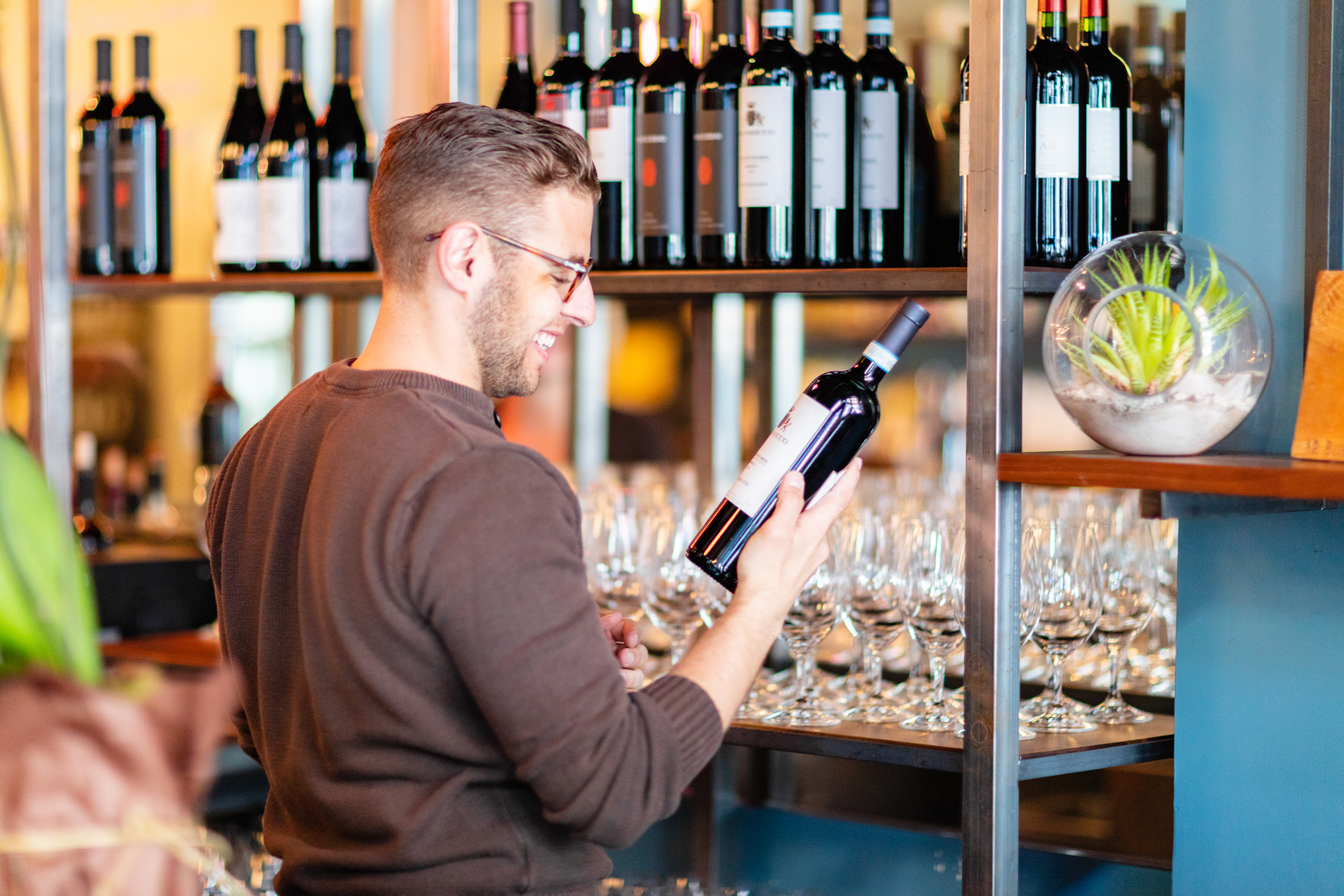 A picture of a man with a small beard and glasses holding a bottle of wine in the bottle shop of Park Avenue Fine Wines