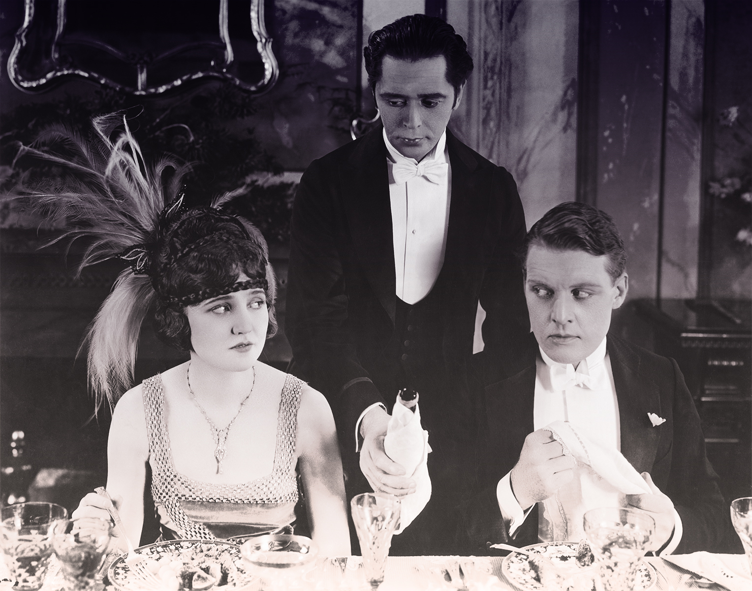 A man and a woman dressed up for a 1920s dinner party give each other the side eye as a waiter reaches between them awkwardly to refill their wine.