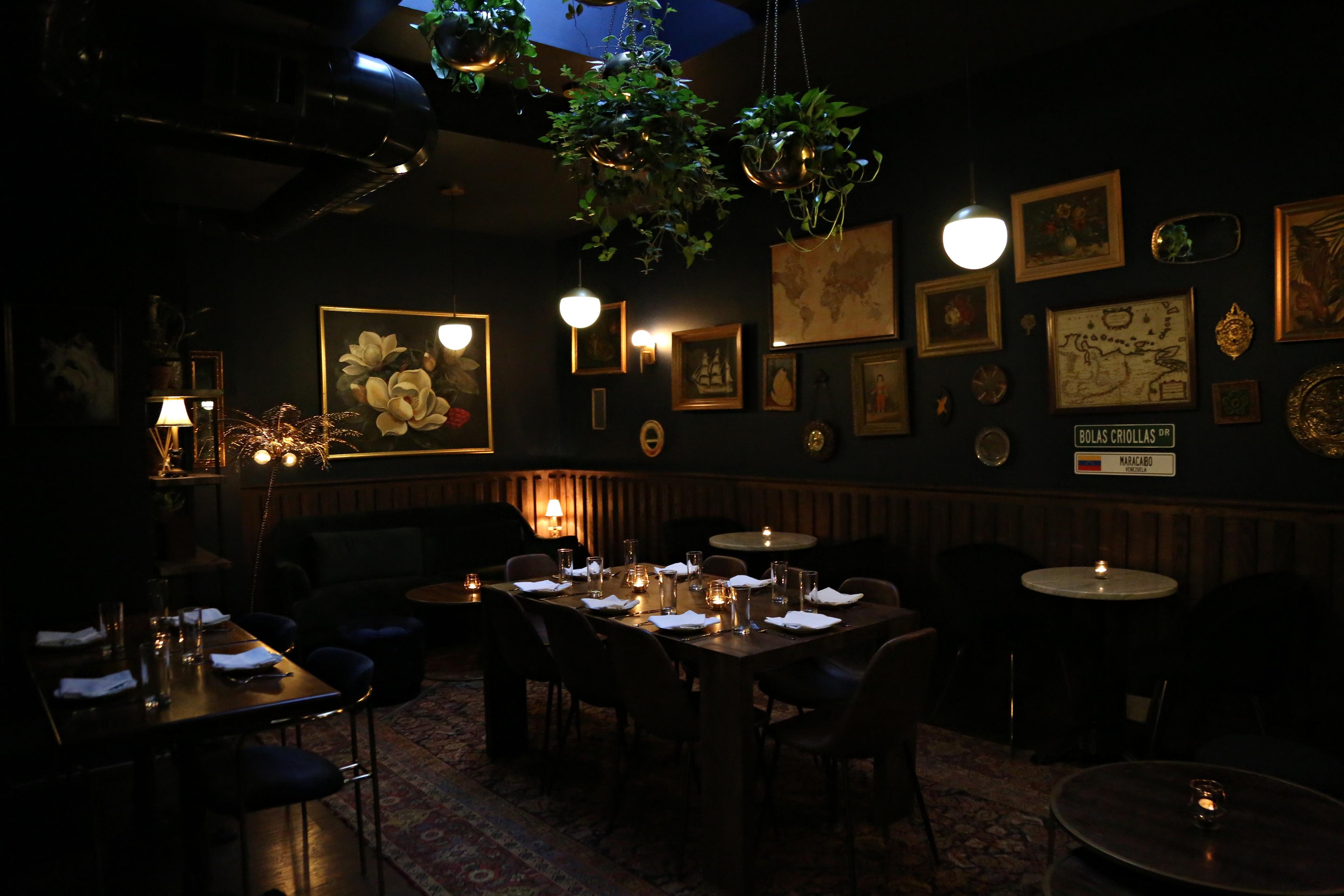 Inside Casa Ora, a dark library-style dining room