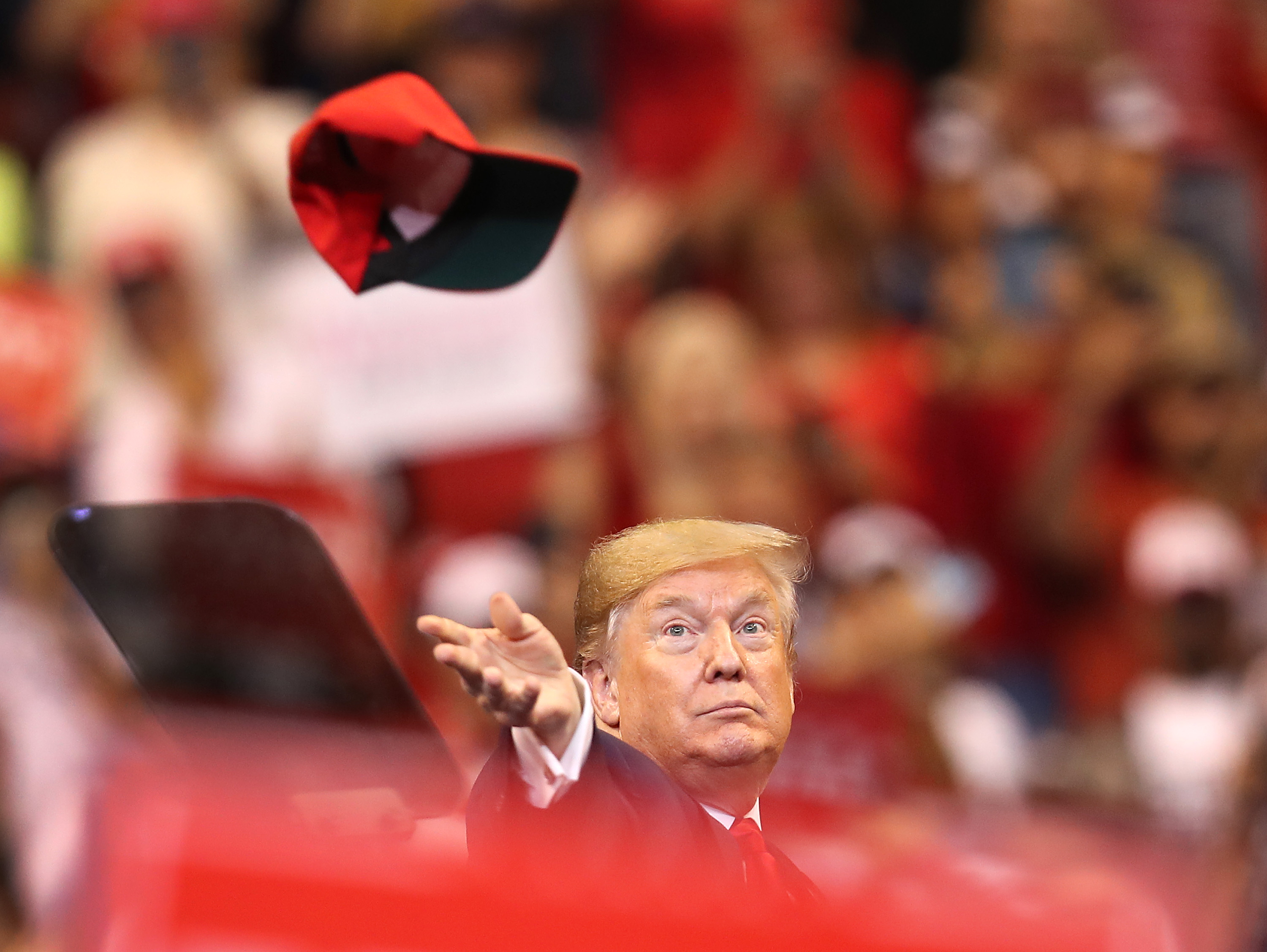President Donald Trump tosses a hat into the crowd at a rally in Sunrise, Florida in November 2019.