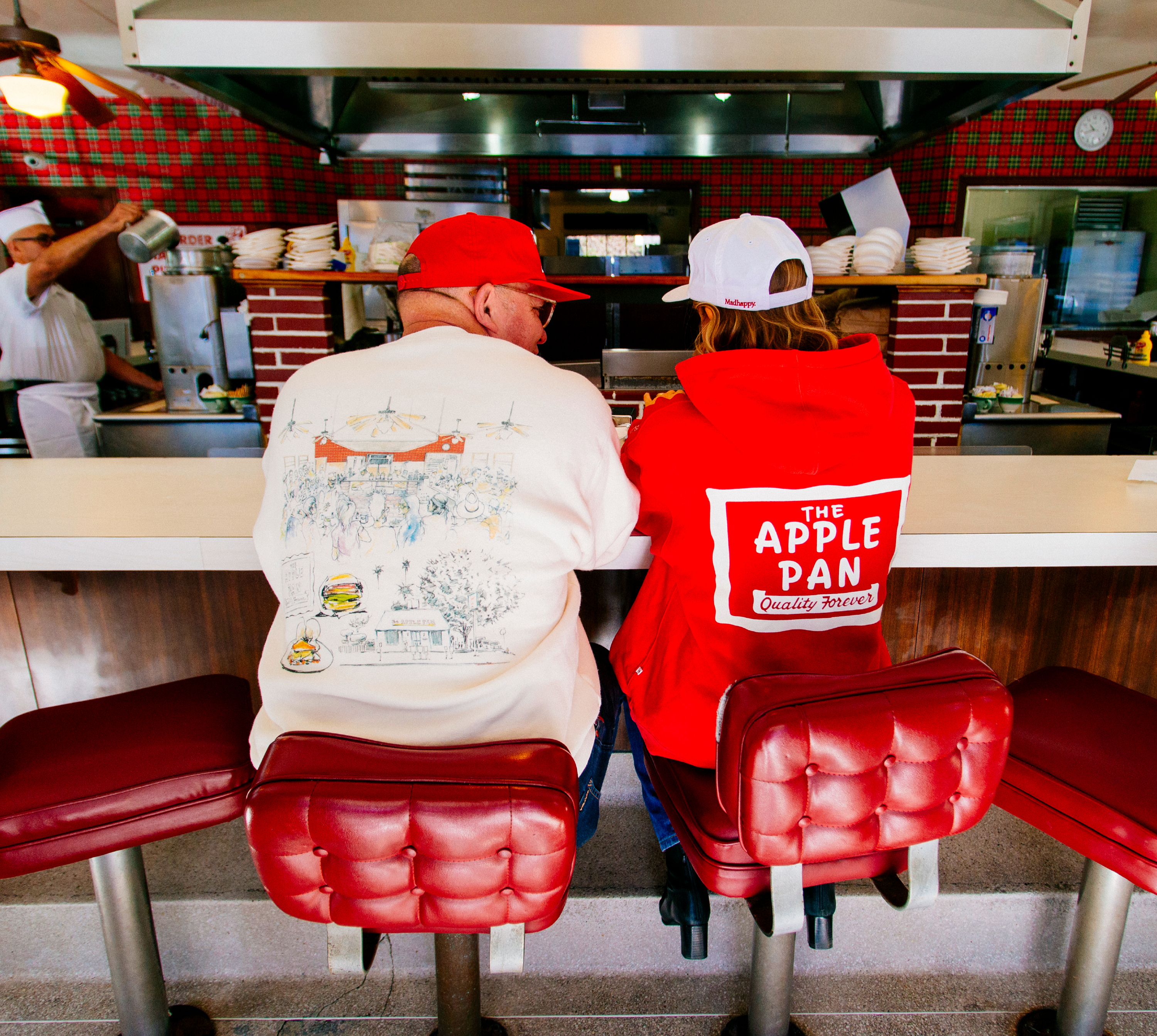 A couple wears Apple Pan branded clothing inside of an old burger restaurant.
