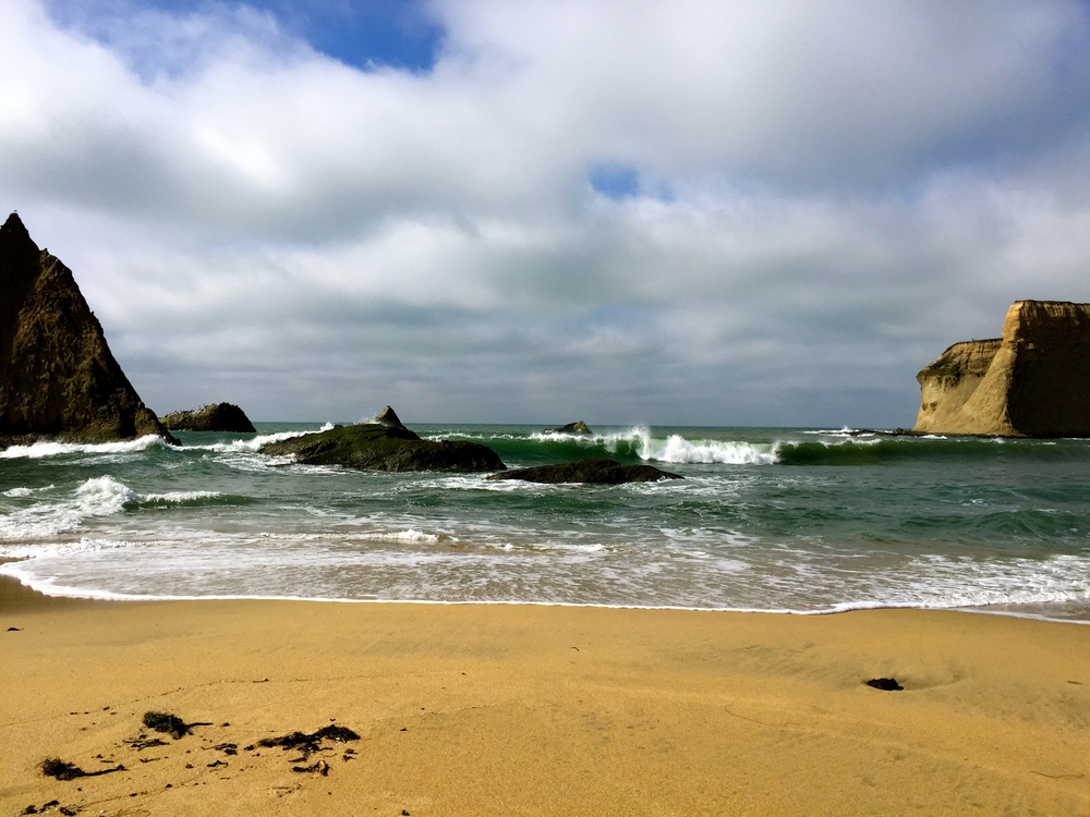 A beach with yellow sand, white waves, blue skies, and rocky outcroppings in the water.
