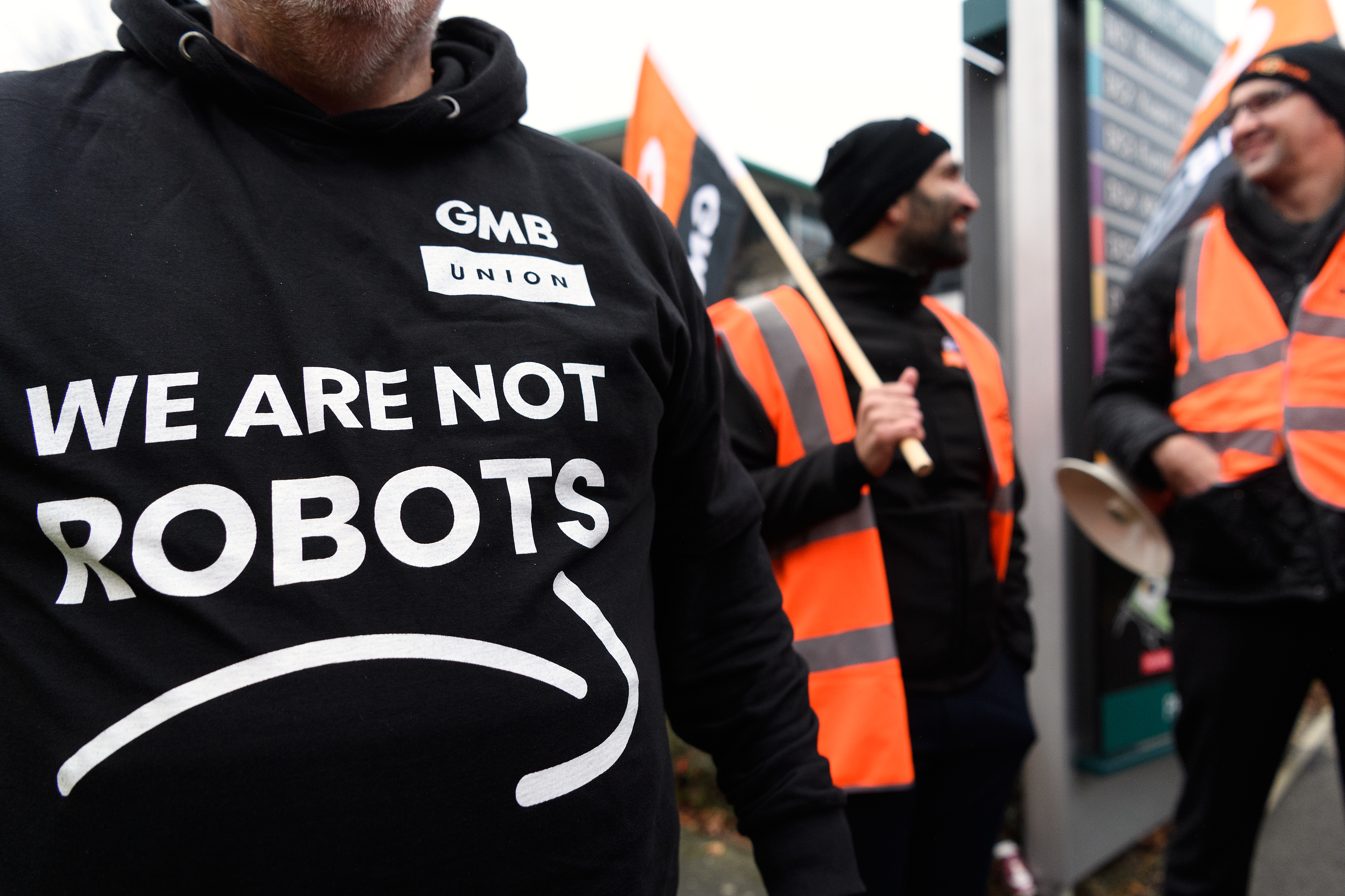 """A close-up of a shirt that says """"We are not robots"""" during a 2018 Black Friday protest outside the Amazon offices."""