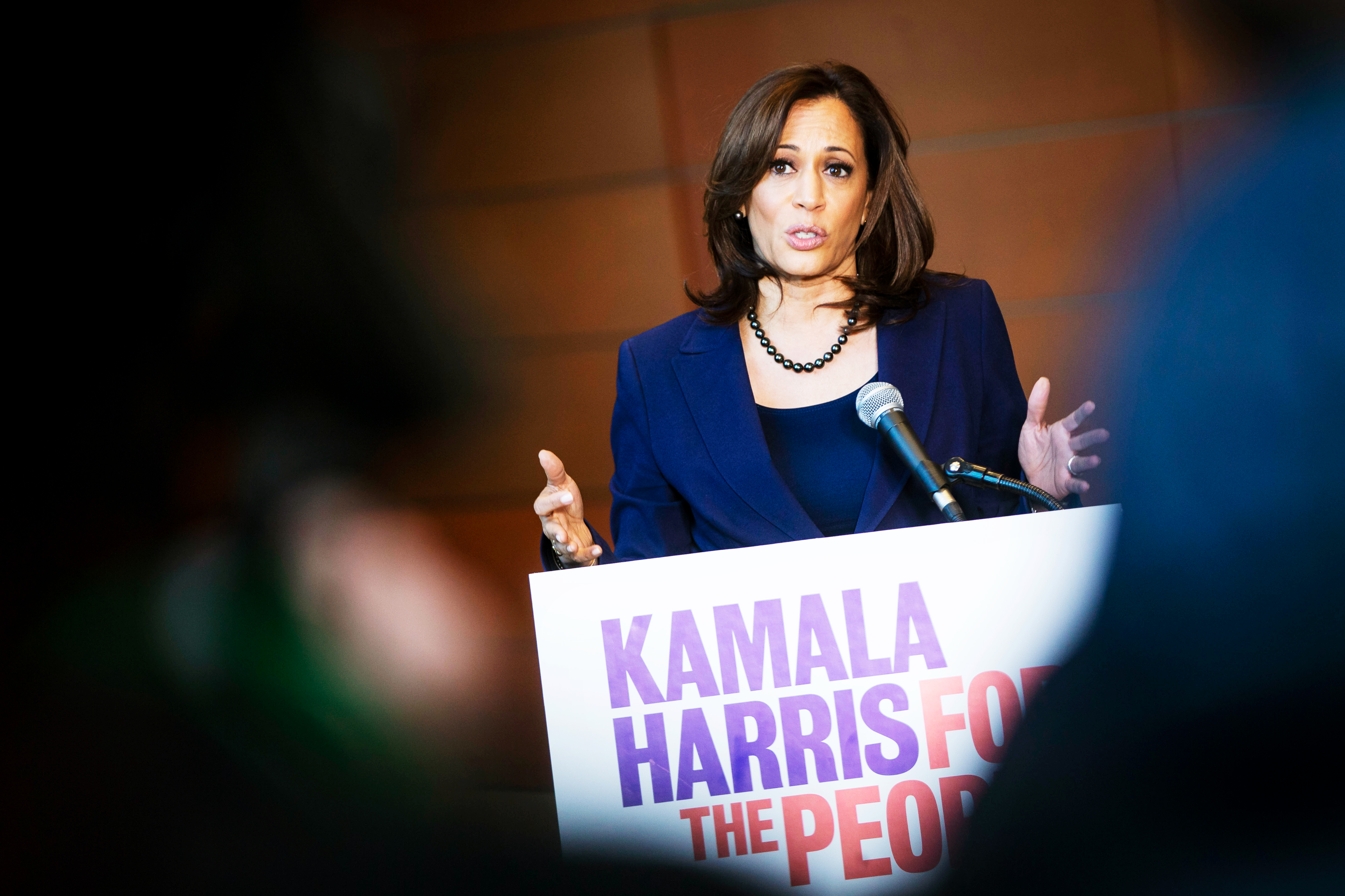 "Senator Kamala Harris speaking from behind a podium with the sign ""Kamala Harris for the people."""