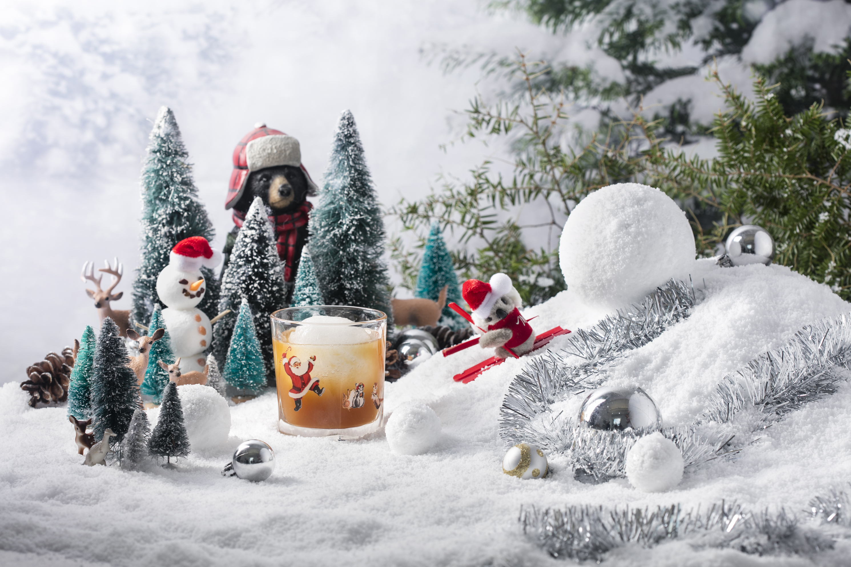This snowy tableau shows a koala on skis, a snowman, a bear in a hunter's outfit, and reindeer overlooking a cocktail glass.