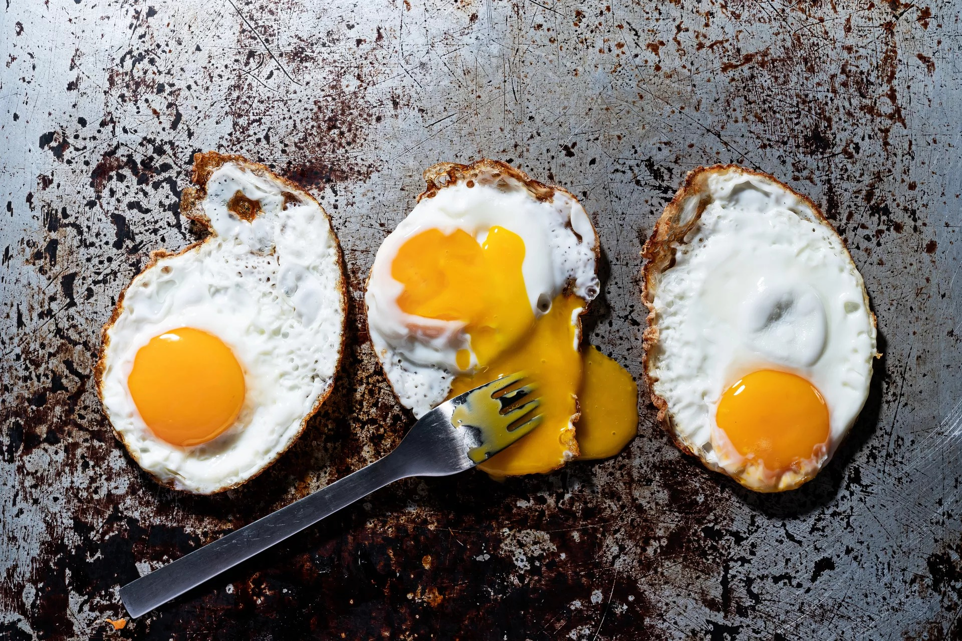Three fried eggs on a griddle, one with its yolk broken by a fork.