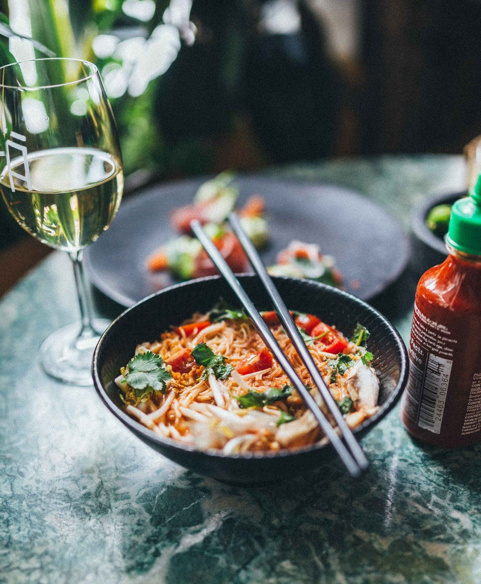 A bowl of Vietnamese soup next to a glass of wine on a table.