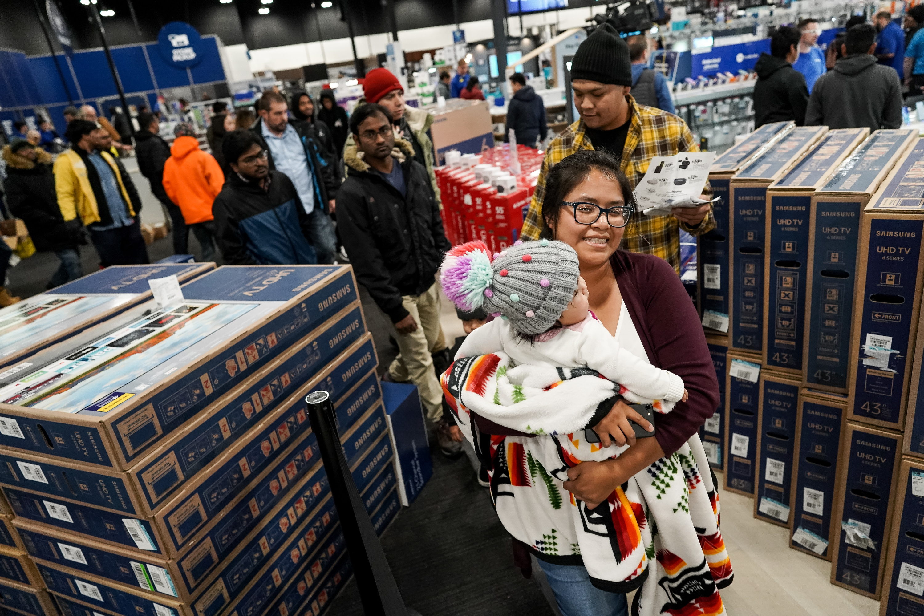 Tara Gishie carries her daughter, Lerayah, 7 months, as while Lemanuel, back right, and Calum, 4, follow behind during Black Friday shopping at Best Buy in Salt Lake City on Thanksgiving Day, Thursday, Nov. 28, 2019.