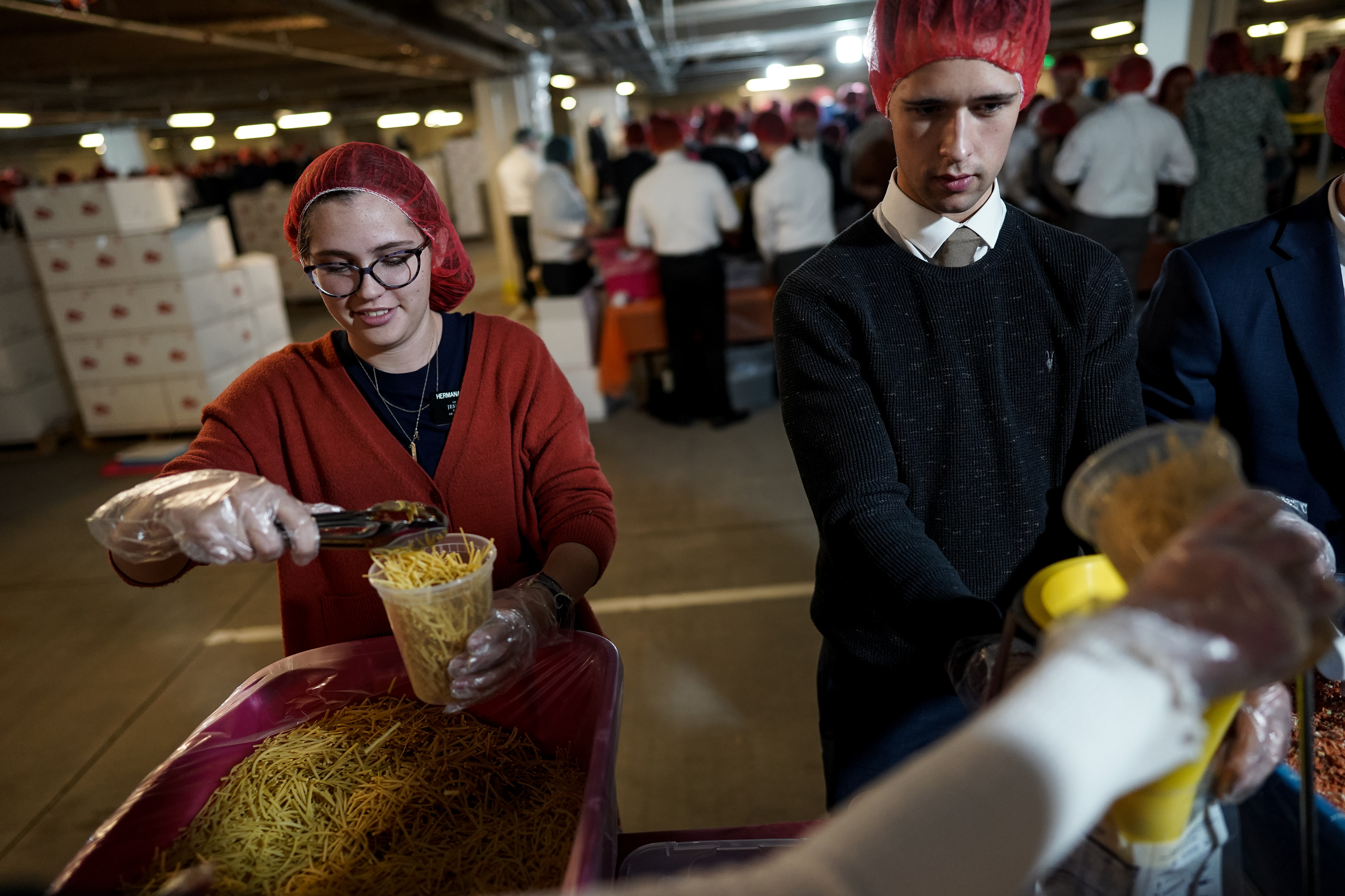 Sister Isabel Galland, 21, of Orem, and Elder Joseph Cottam, 19, of Yorkshire, England, and other missionaries for The Church of Jesus Christ of Latter-day Saints prepare meal donations at the Missionary Training Center in Provo on Thanksgiving Day, Thursday, Nov. 28, 2019.