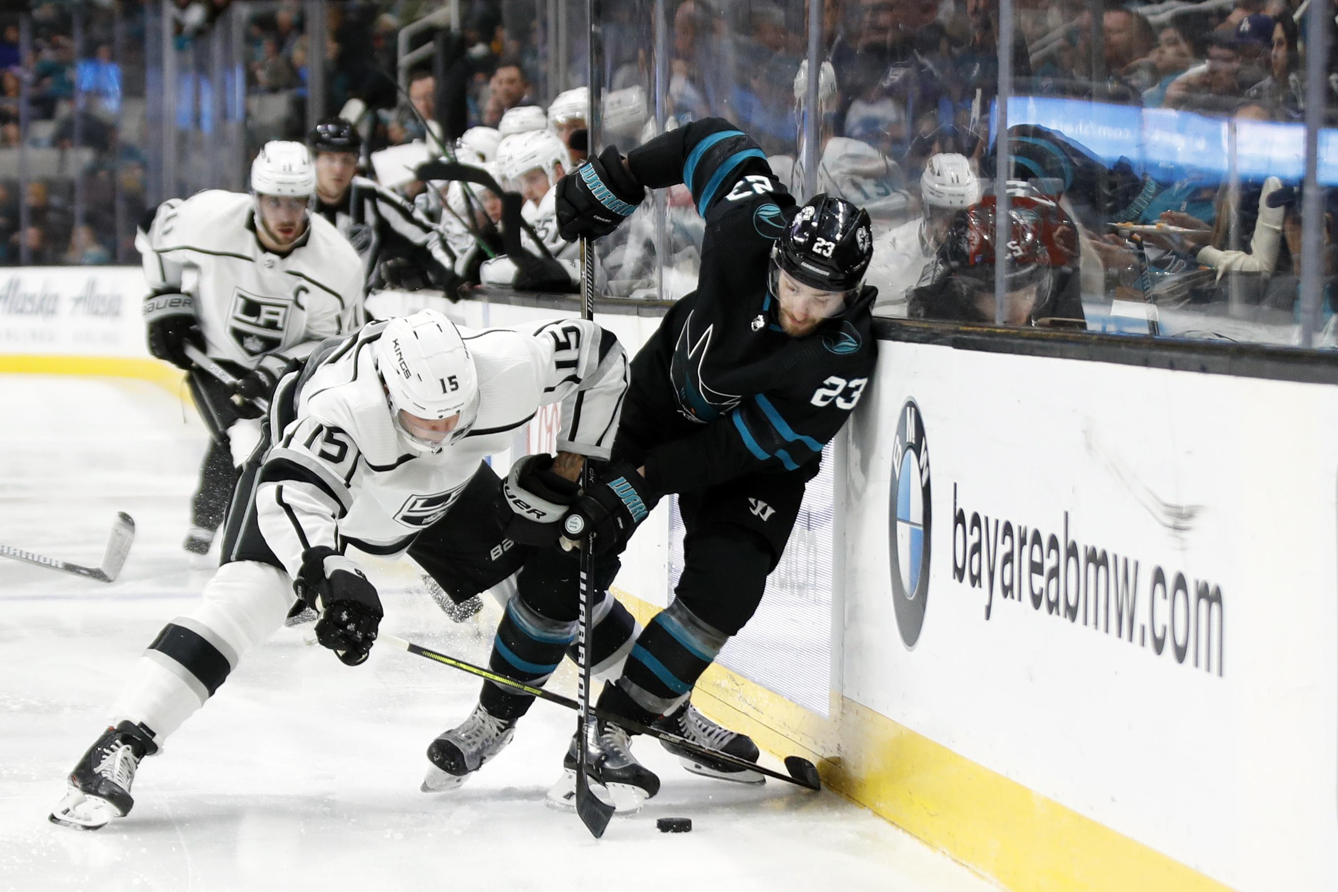 Nov 29, 2019; San Jose, CA, USA; Los Angeles Kings defenseman Ben Hutton (15) and San Jose Sharks center Barclay Goodrow (23) battle along the boards for the puck during the second period at SAP Center at San Jose.
