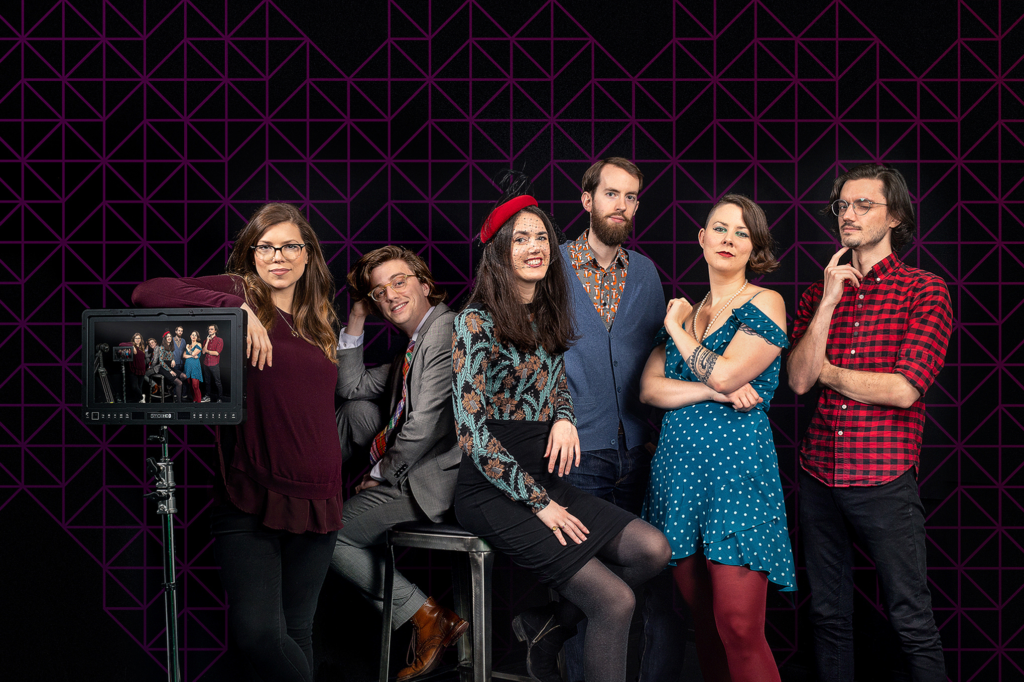 A group photo of the Polygon video team in a dark studio with graphic pattern