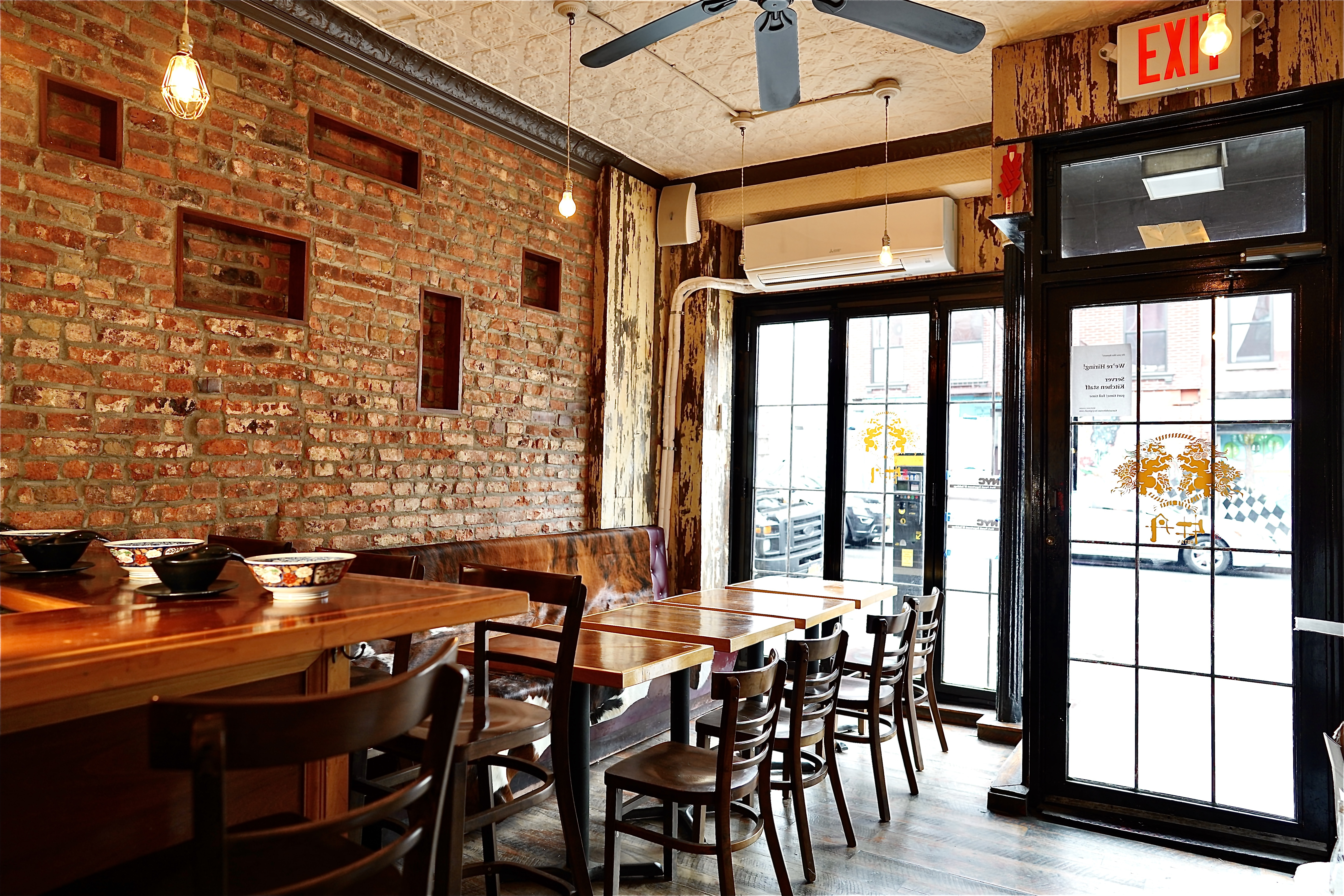 Inside a small restaurant with exposed red brick walls, glass windows with panels and a set of wooden chairs and tables