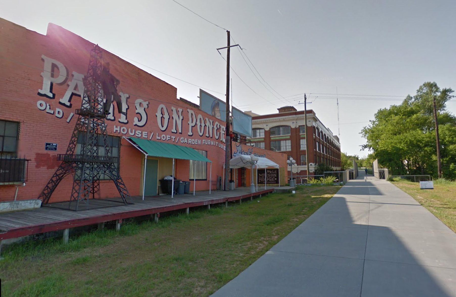 A picture of Paris on Ponce, painted orange with meal artwork on the porch, standing next to the Beltline's Eastside Trail