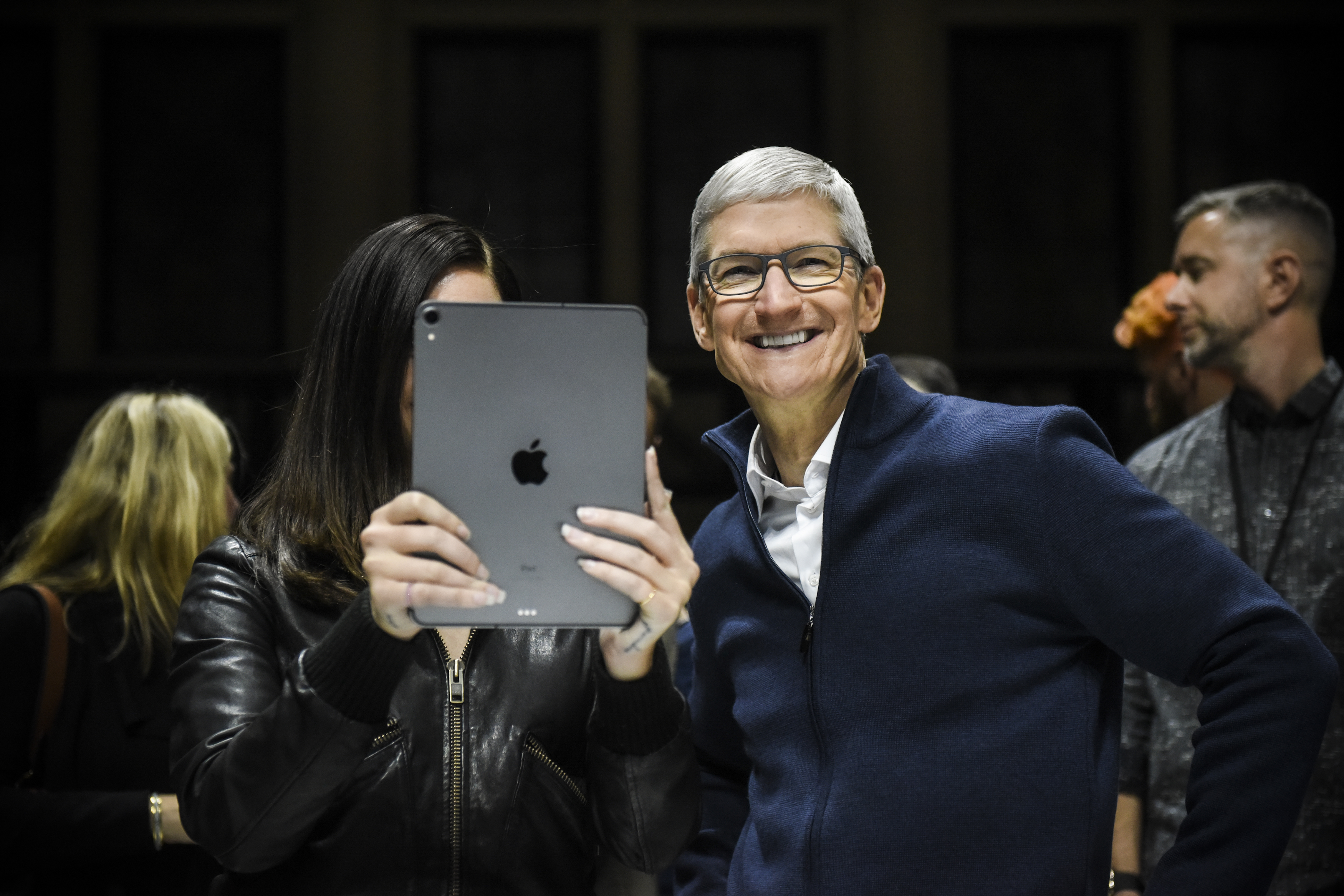 Apple CEO Tim Cook smiles beside singer Lana Del Rey as she holds up an iPad.