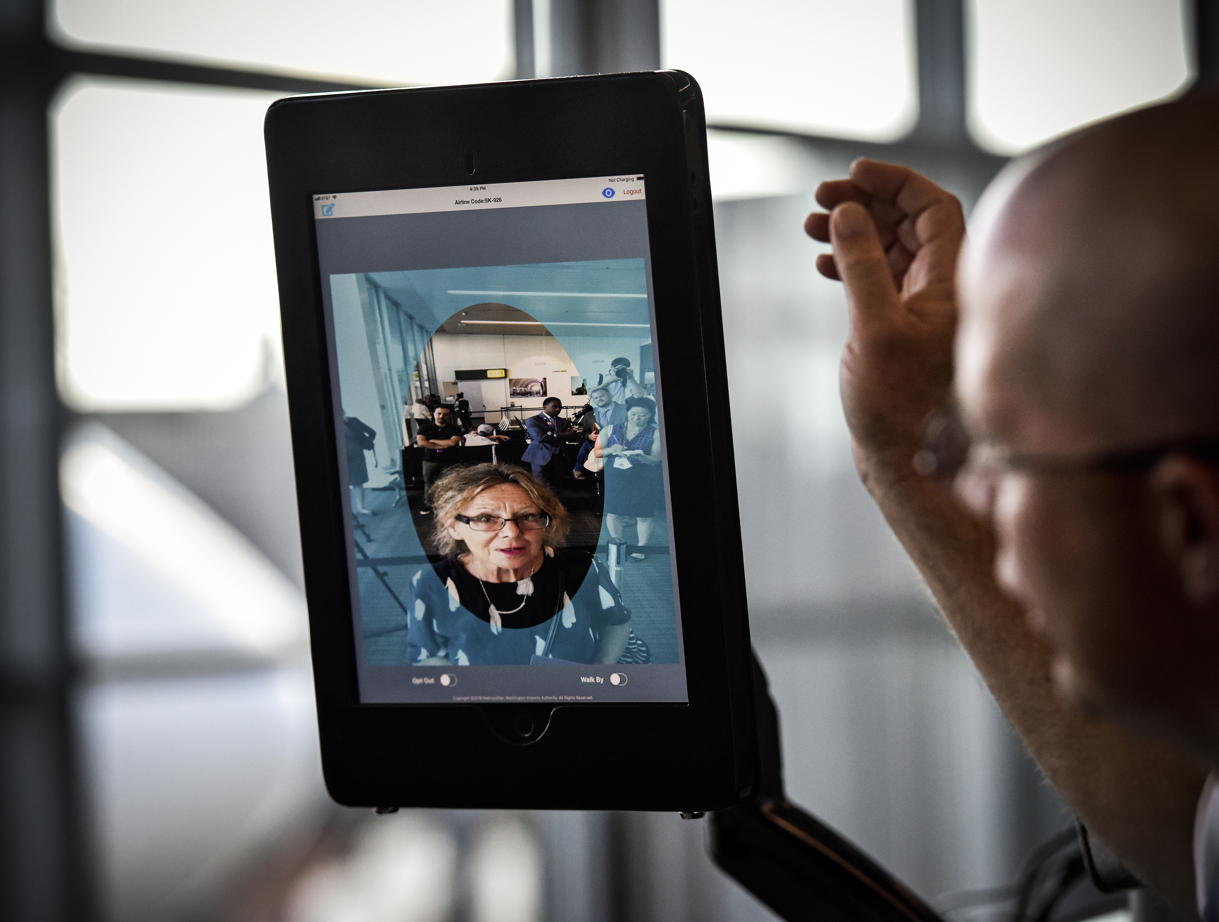 A man looks at a screen that is trying to recognize his facial features.