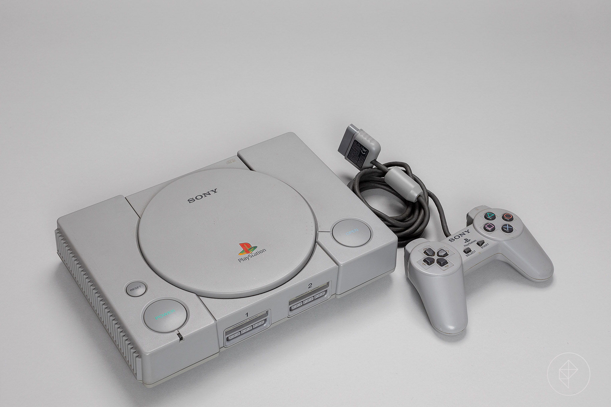 The original Playstation and controller shot on a grey background
