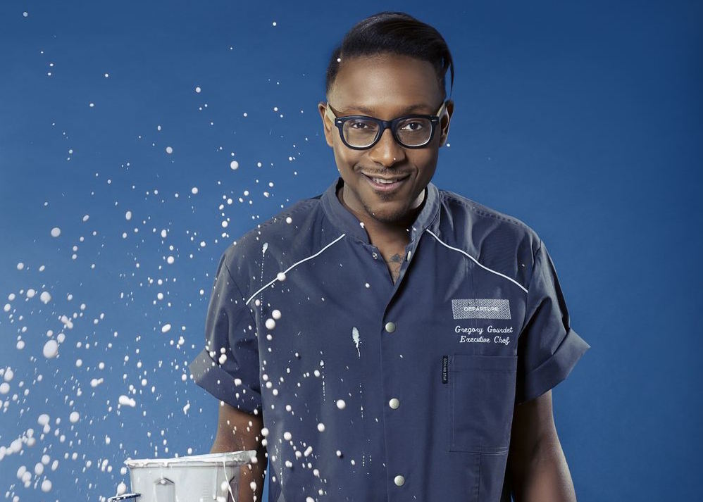 A picture of Gregory Gourdet, the chef at Departure, wearing his uniform as an open blender sprays liquid everywhere