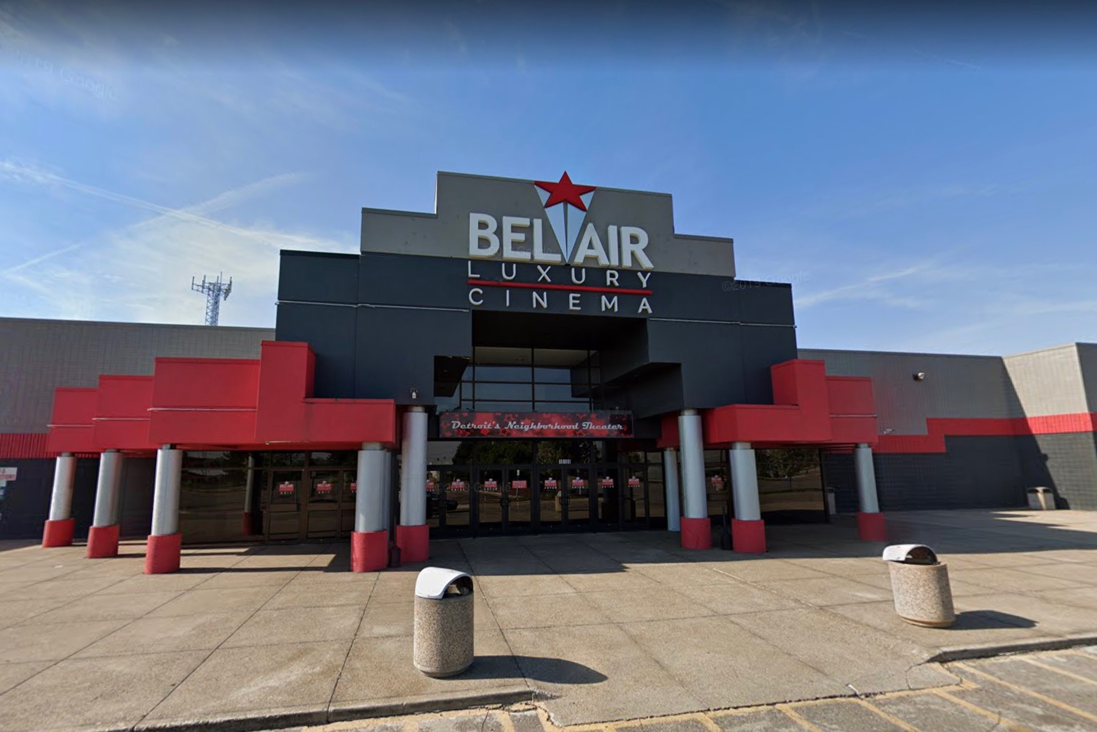 """Front of a red and black movie theater. Over the glass entrance a sign reads """"Bel Air Luxury Cinema."""""""