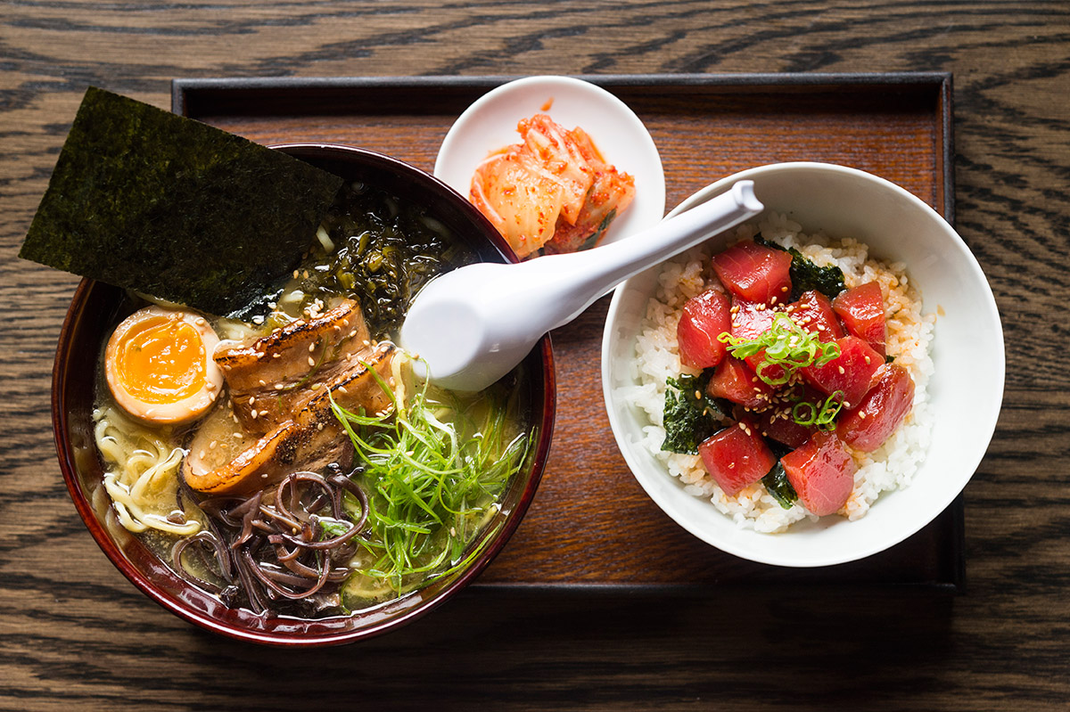 A bowl of ramen, a small bowl of kimchi, and a plate of tuna poke on a wooden tray
