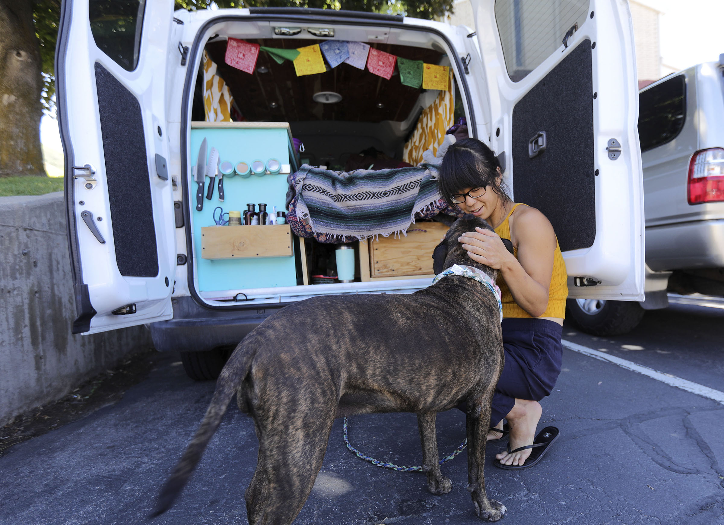 Kathy Karlo pets her dog Shooter McGavin outside of her van, where she is currently living, in Cottonwood Heigh on Tuesday, July 2, 2019.
