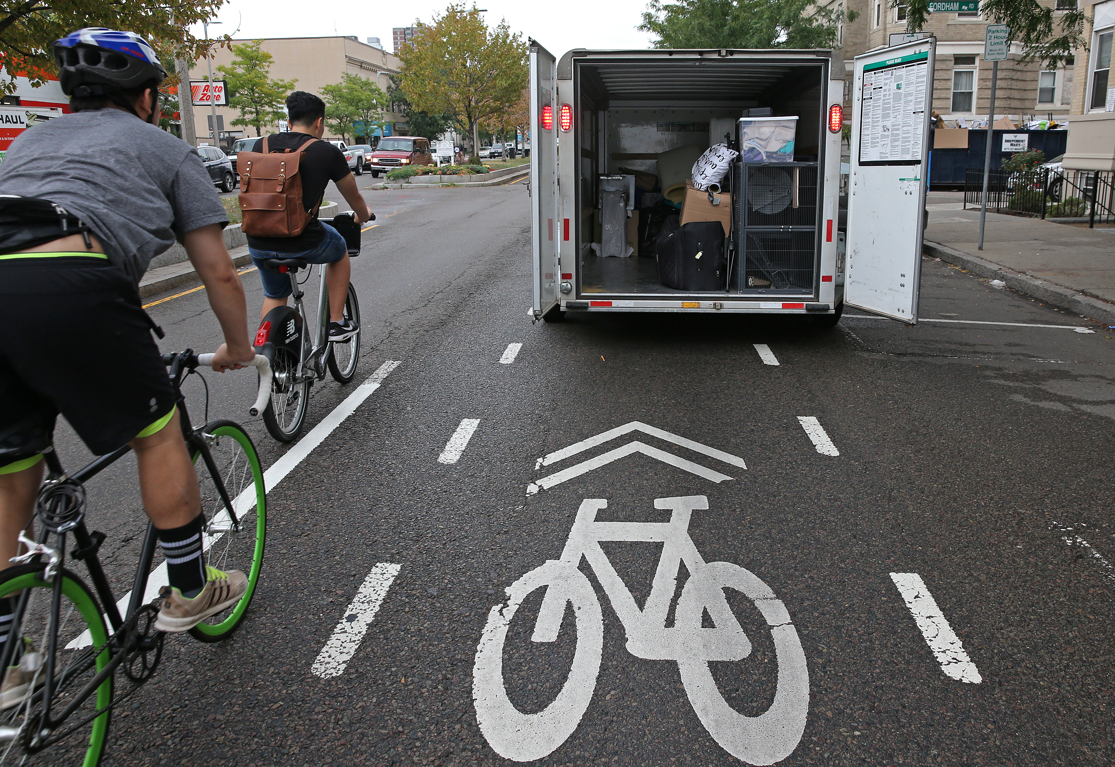 Bikers make their way around a delivery truck parked in a bike lane.