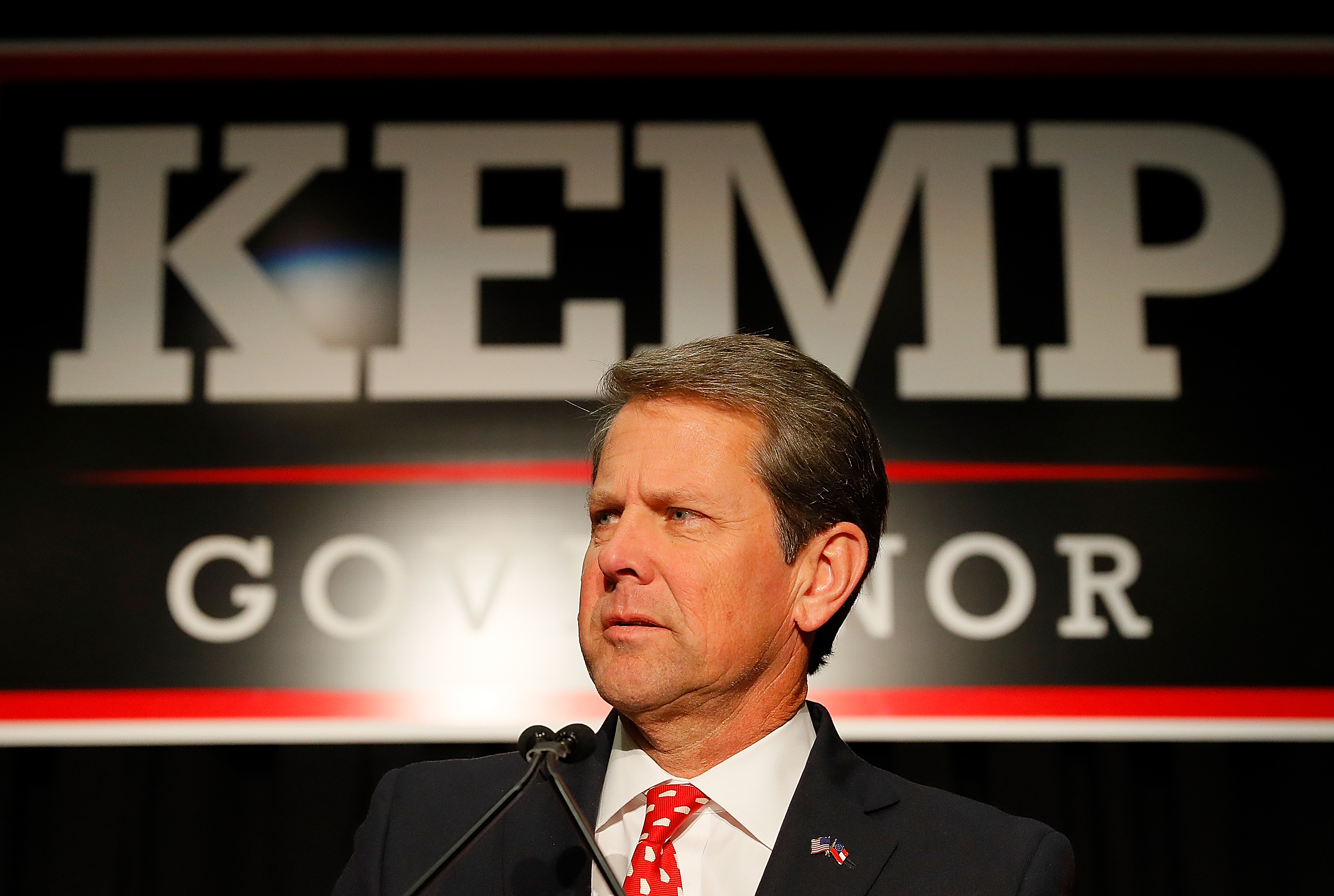 "Georgia Governor Brian Kemp standing in front of a ""Kemp for governor"" sign."