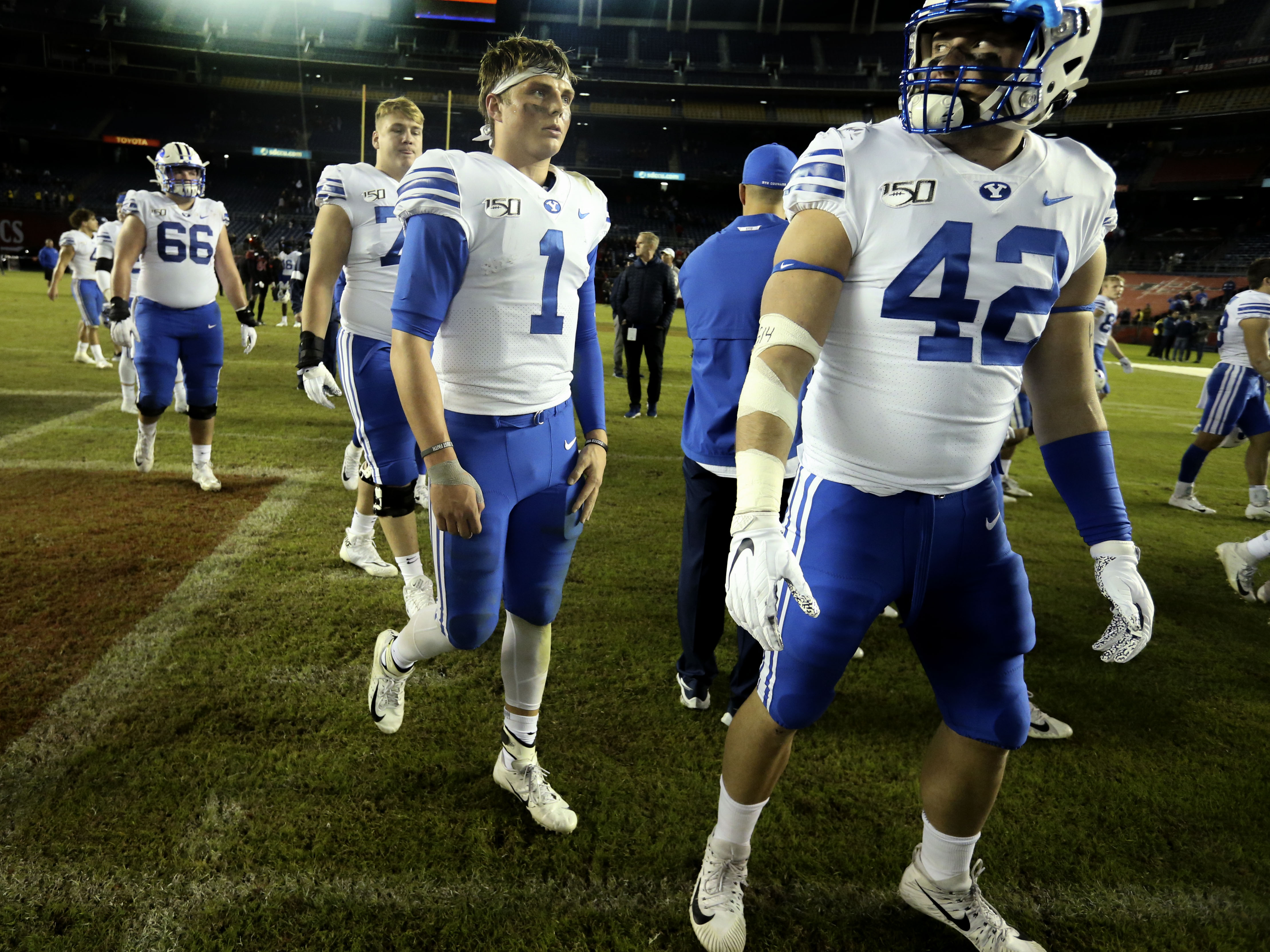 BYU football players, including quarterback Zach Wilson (1) and tight end Kyle Griffitts (42), leave the field after losing to the San Diego State Aztecs at SDCCU Stadium in San Diego on Saturday, Nov. 30, 2019.
