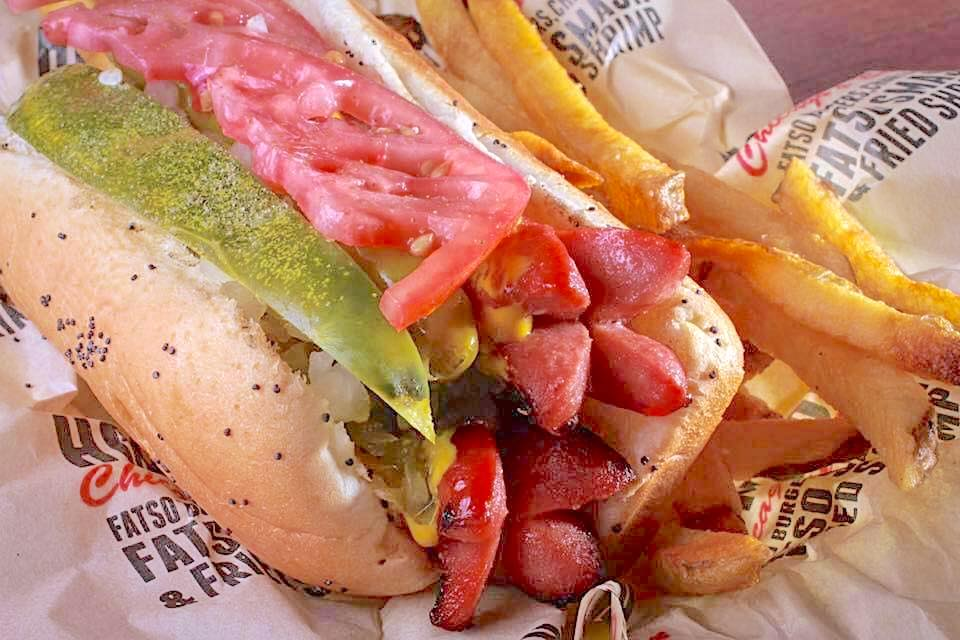 A Chicago-style char dog on a bun with french fries.