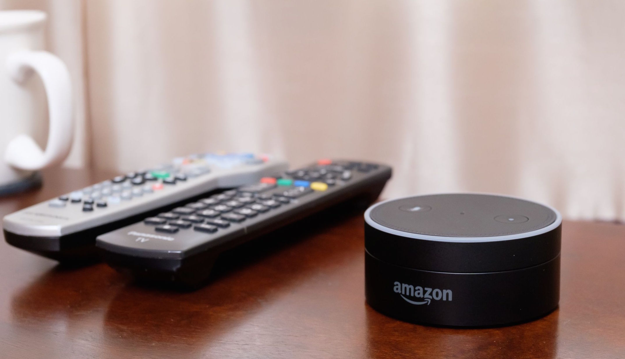 Amazon Echo Dot on a table beside a pair of TV remotes.