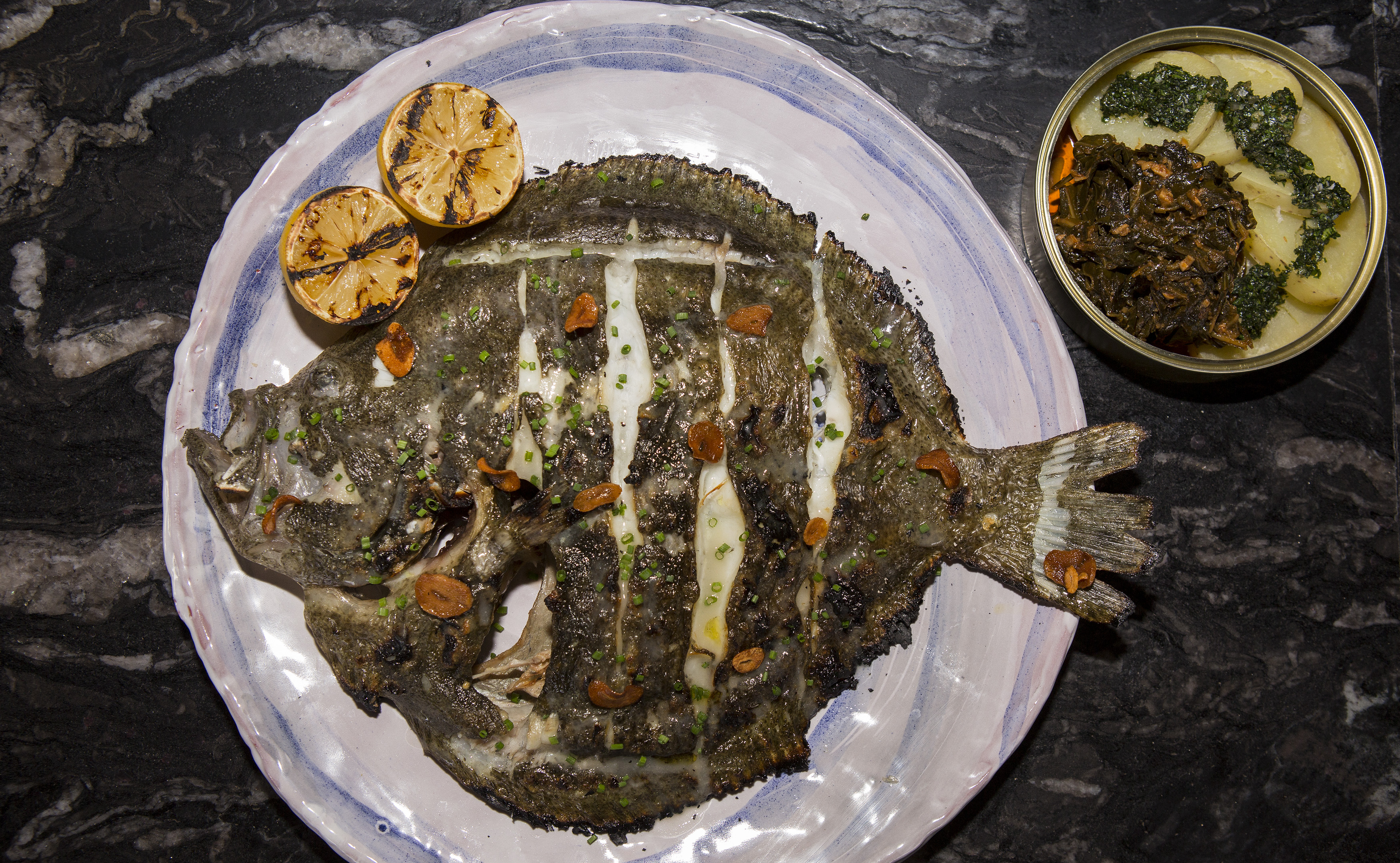 A large grilled whole fish on an intricate plate with a sides in a tin can.