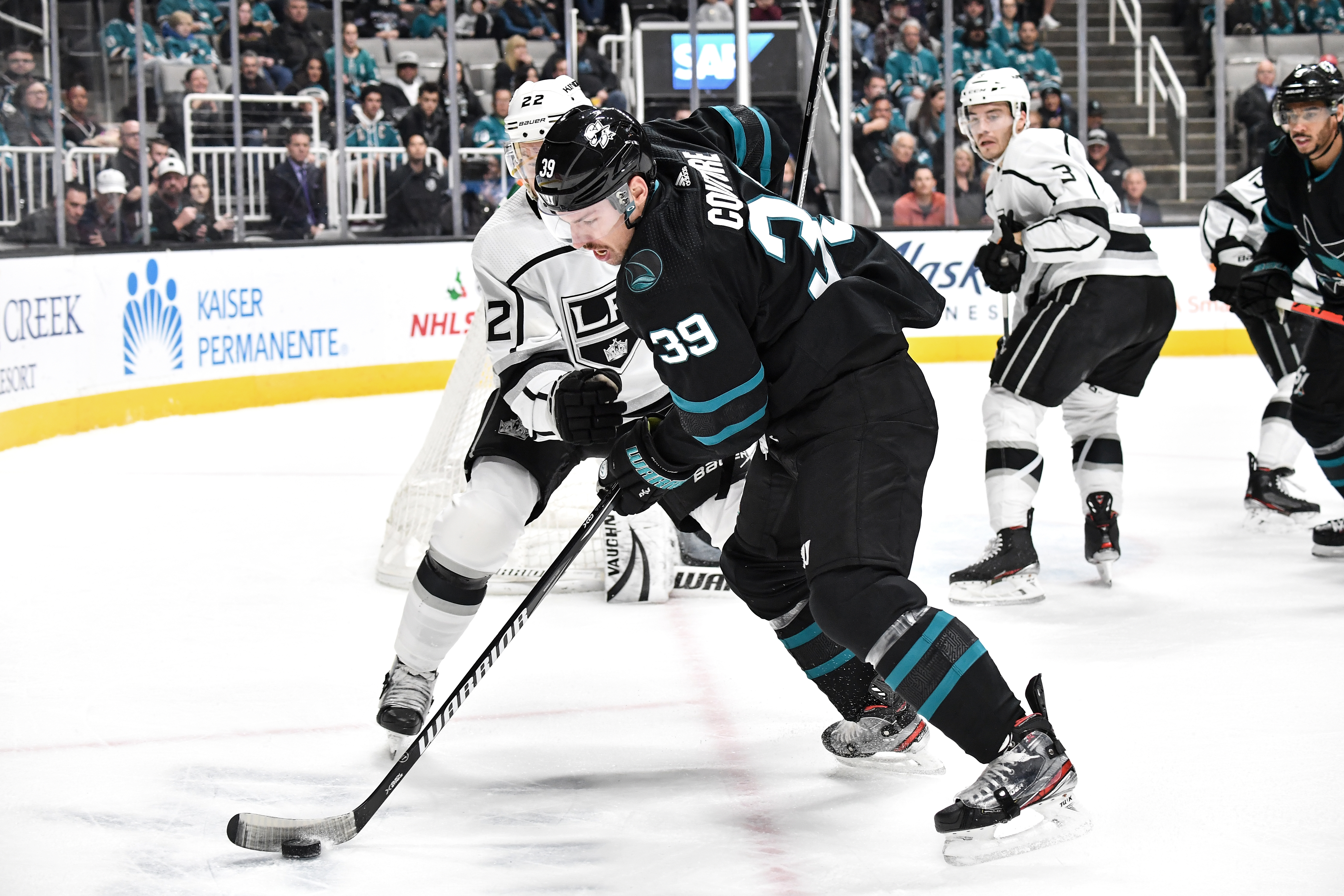 SAN JOSE, CA - NOVEMBER 29: Logan Couture #39 of the San Jose Sharks battles for the puck against Trevor Lewis #22 of the Los Angeles Kings at SAP Center on November 29, 2019 in San Jose, California.