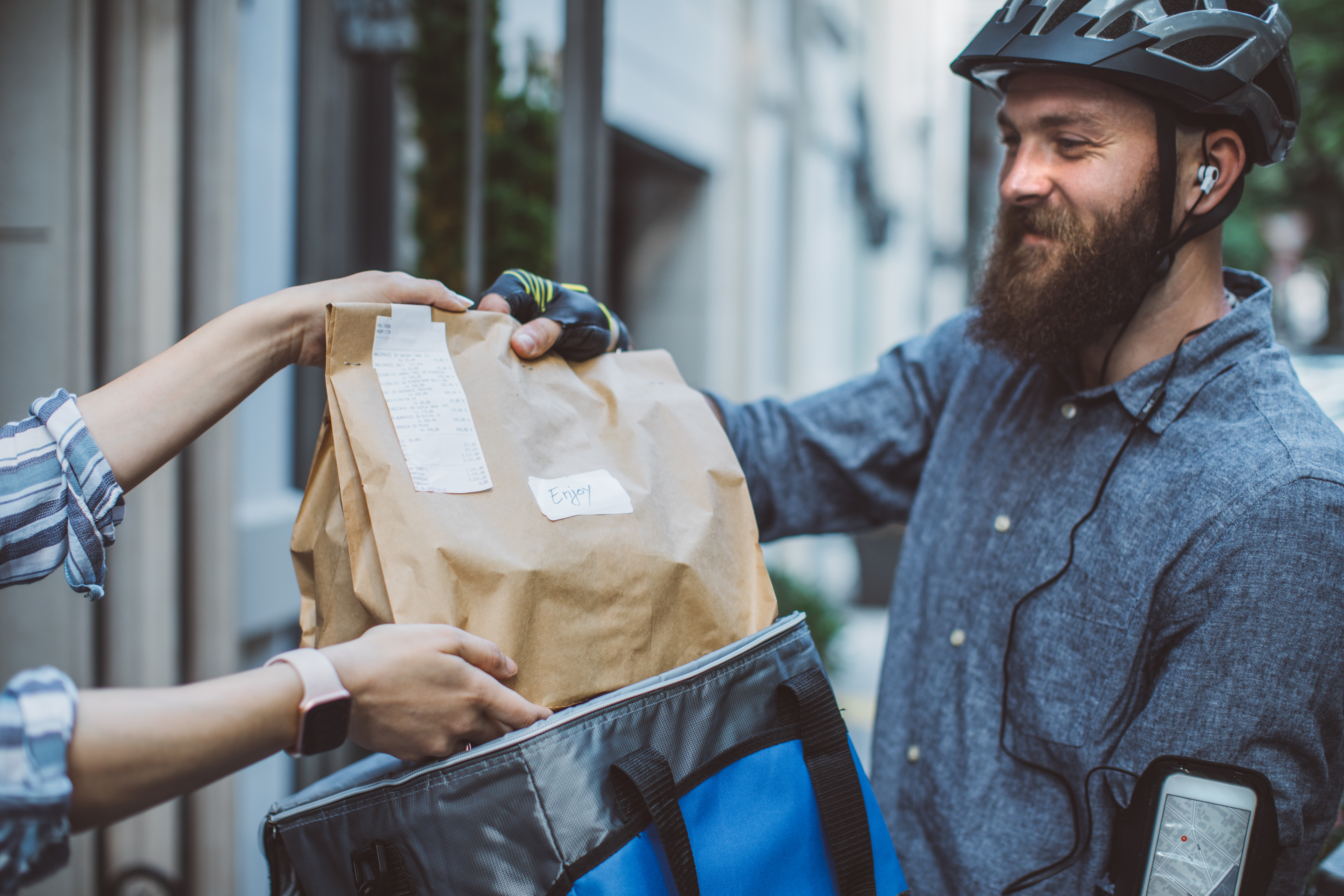 A delivery worker in a bike helmet handing a bag of food to a customer.