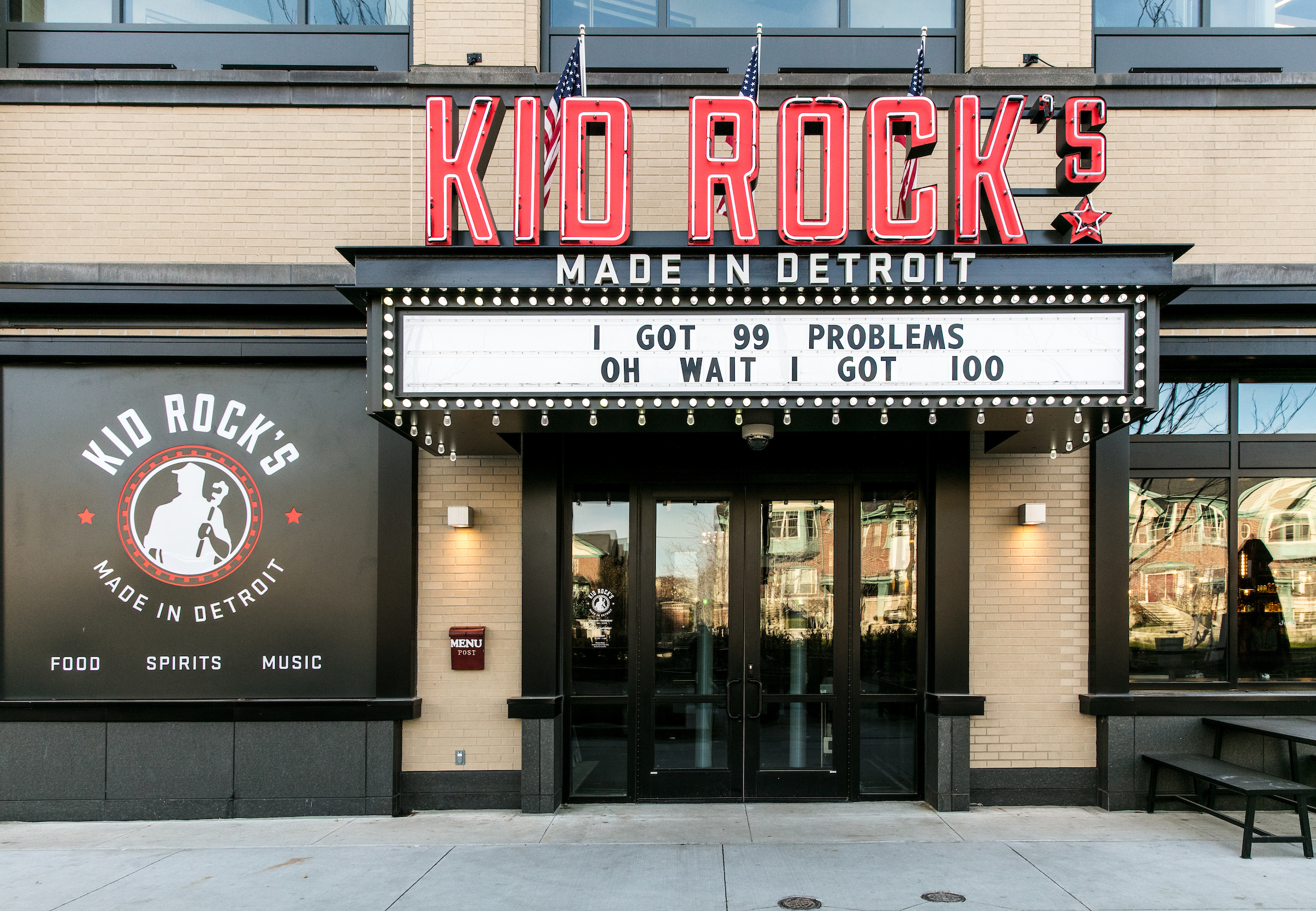 "Neon signage on the exterior of Kid Rock's Made in Detroit restaurant with a marquee reading ""I've got 99 problems. Oh wait I've got 100."""
