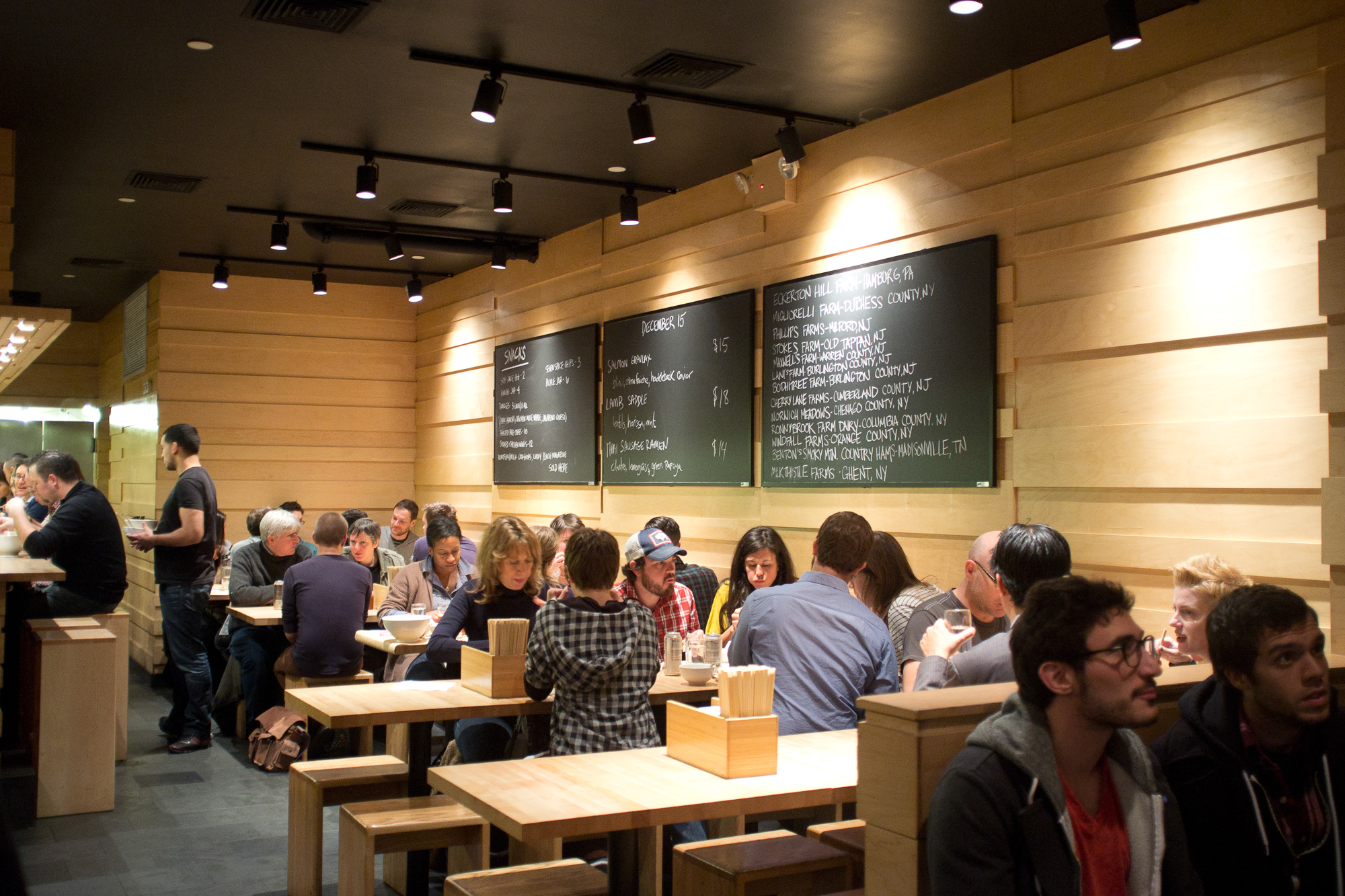 People dining inside Momofuku Noodle Bar's wood-filled interior