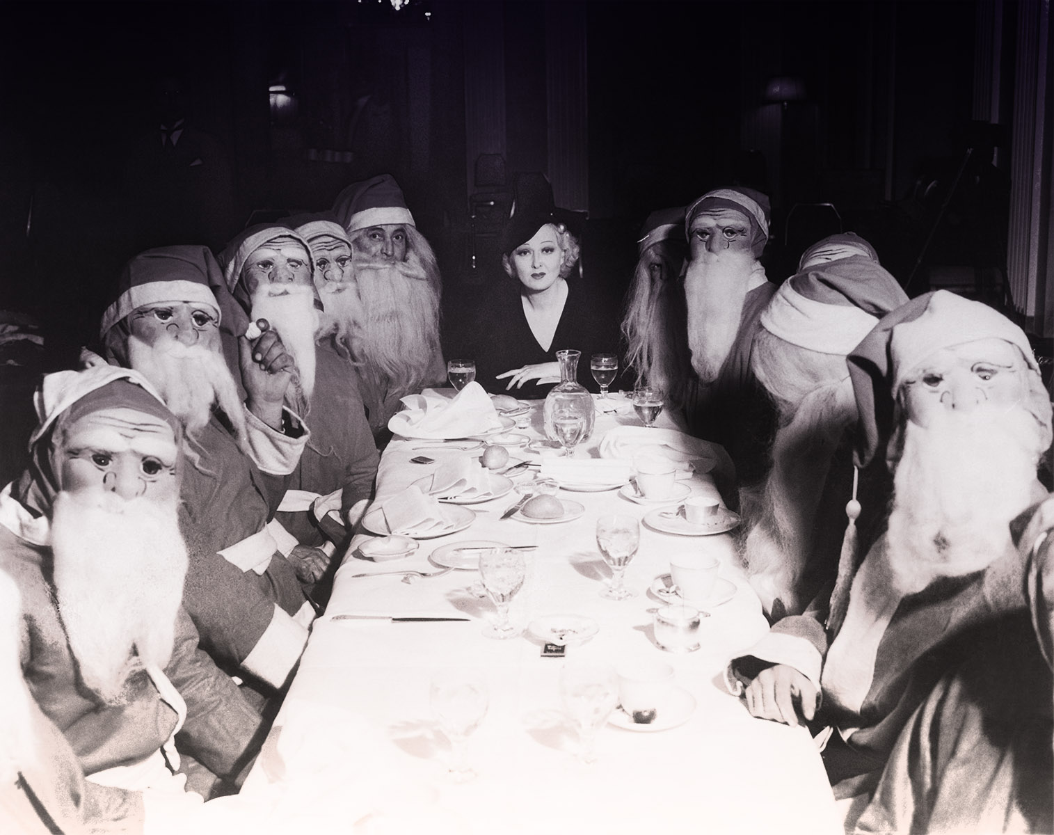 A vintage black and white photo features a woman in a hat at one end of a long table surrounded by men in horrifying santa masks.