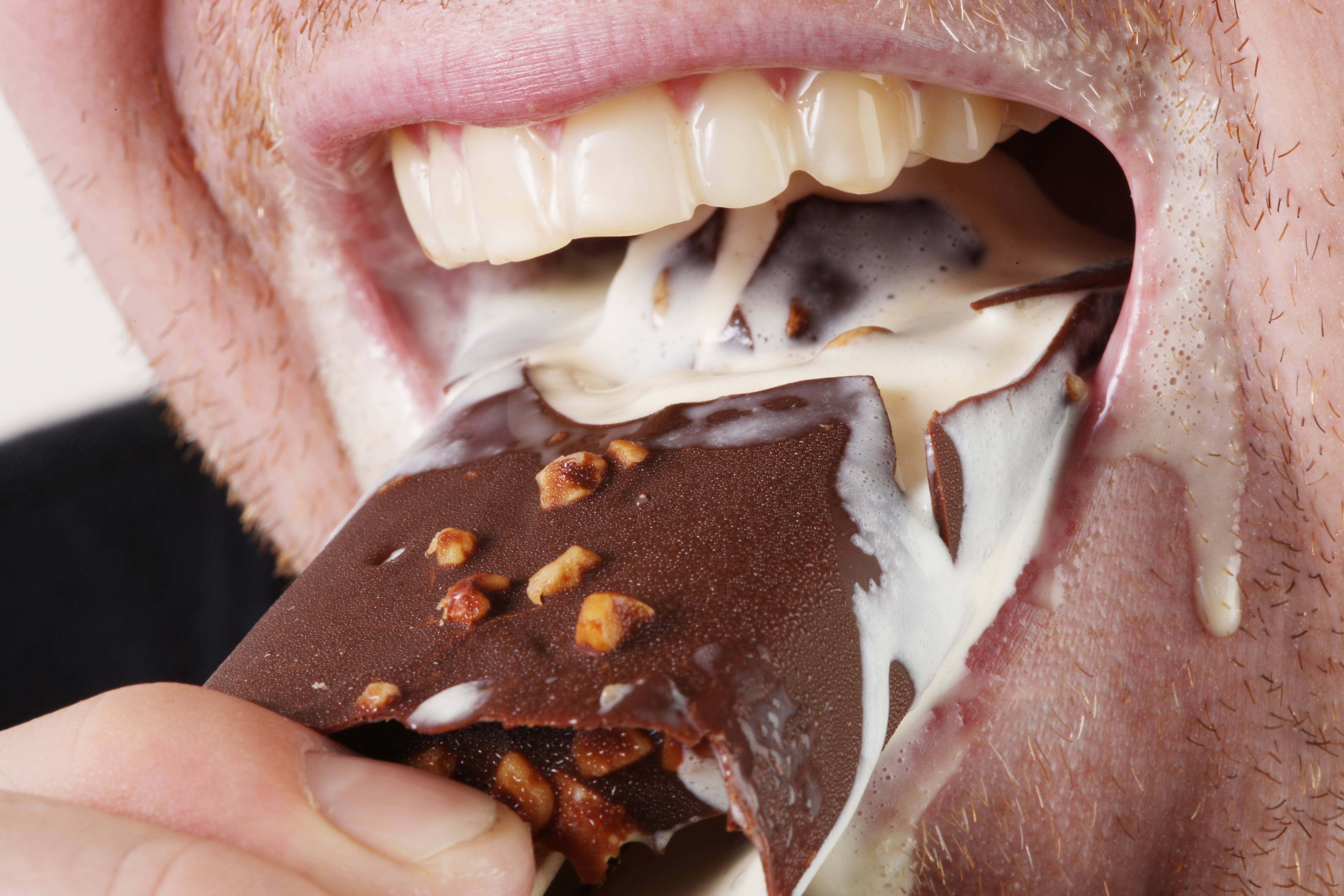 Close up of an unshaven man eating an ice cream bar