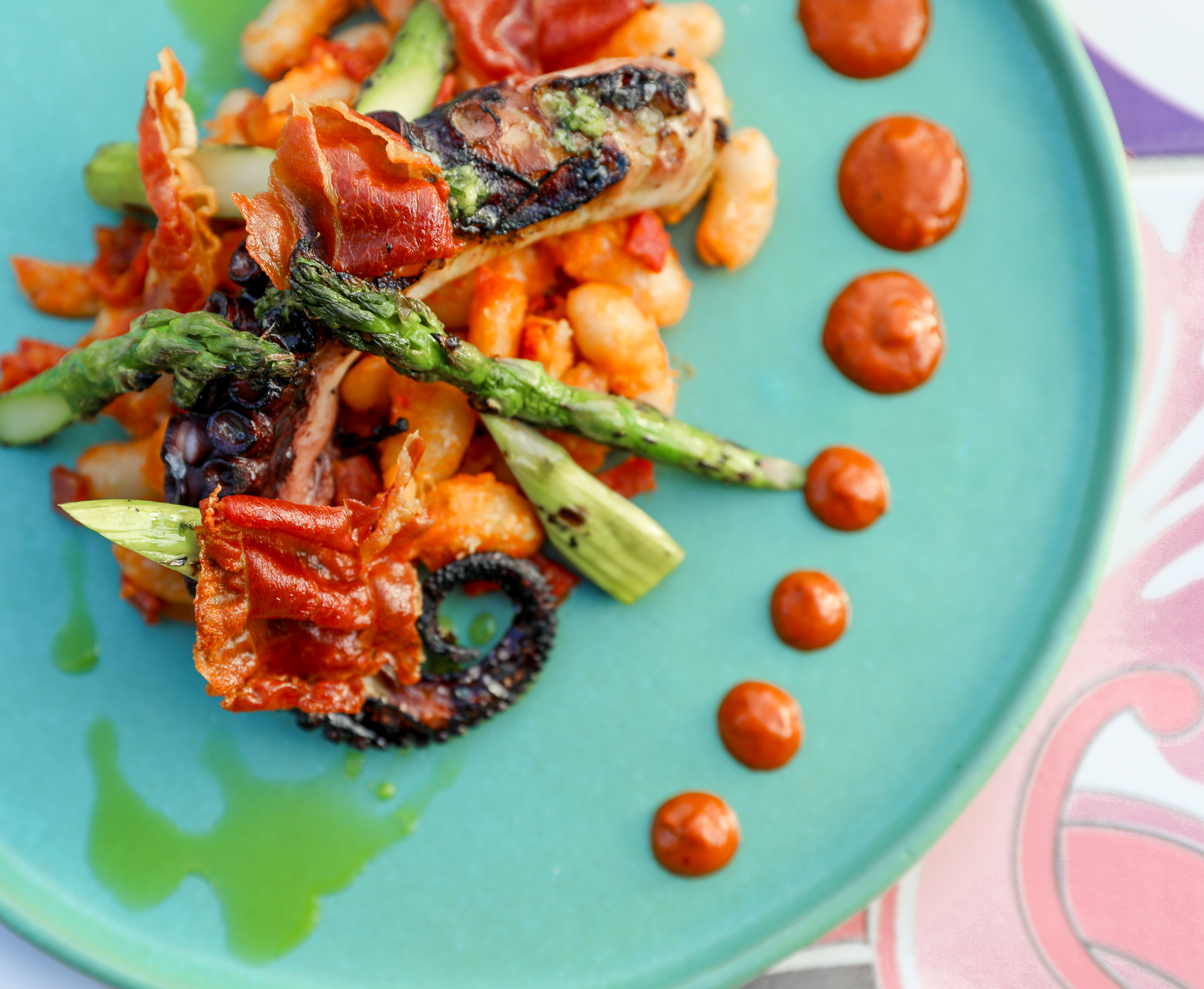 A blue plate with grilled octopus and asparagus at Buena Vida Tapas
