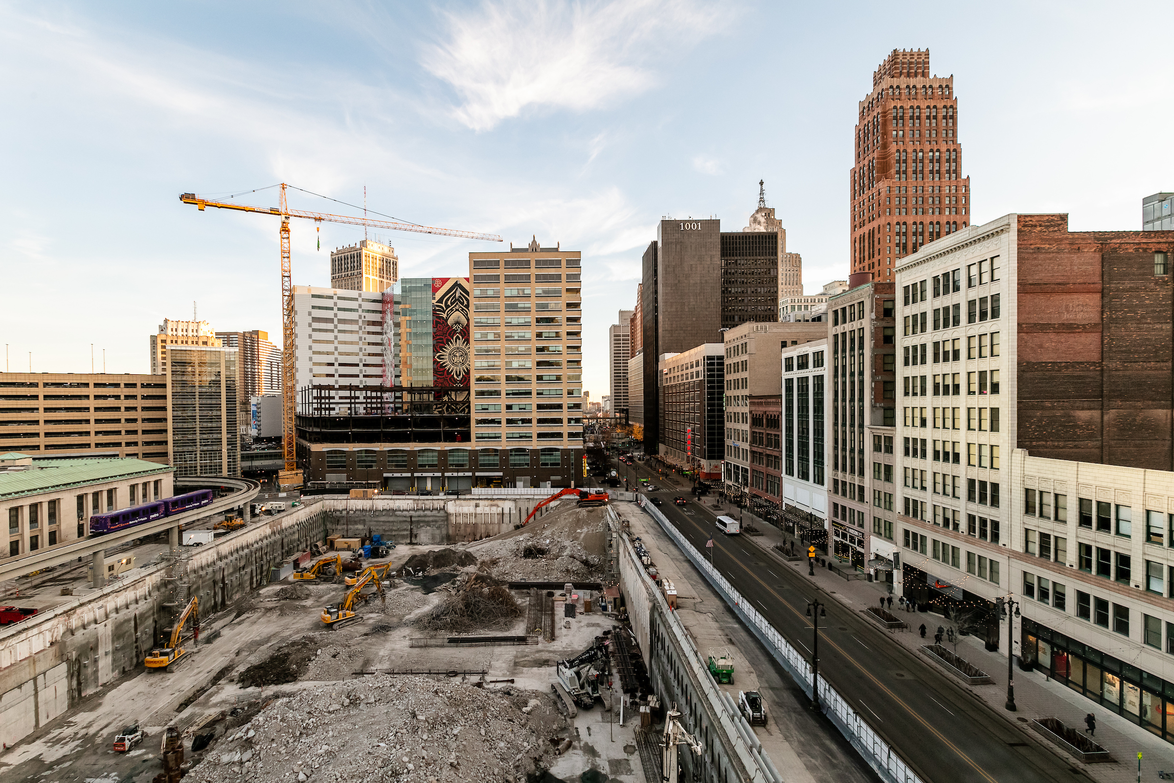 A tall crane sits next to a large dig site in the middle of a downtown.