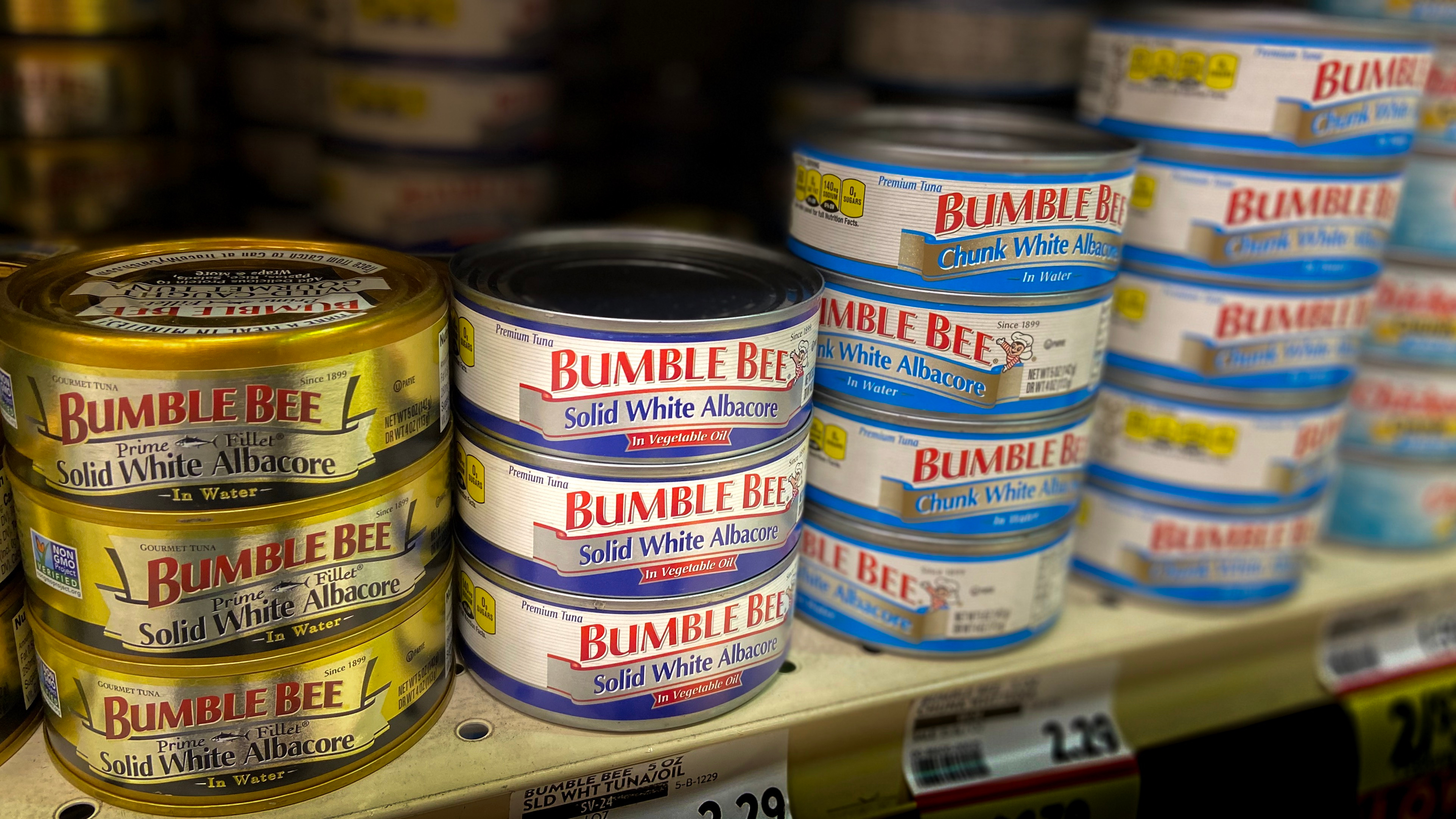 Stacks of Bumble Bee canned tuna on a grocery store shelf.