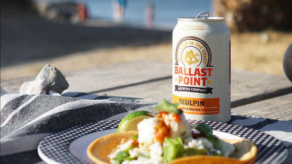 A can of Ballast Point beer on a wooden table beside a plate of food.
