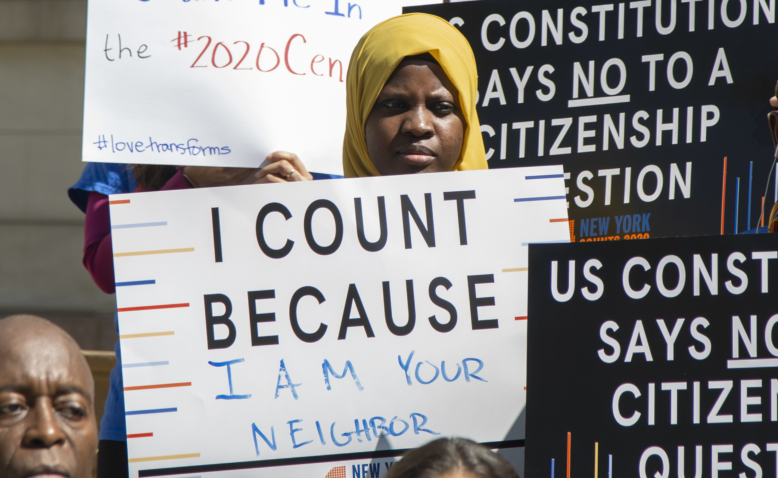 """A black woman wearing a headscarf holds a poster that reads: """"I count because I am your neighbor"""" and is surrounded by signs that say: """"US Constitution Says No To Citizenship Question"""" during a press conference in NYC"""