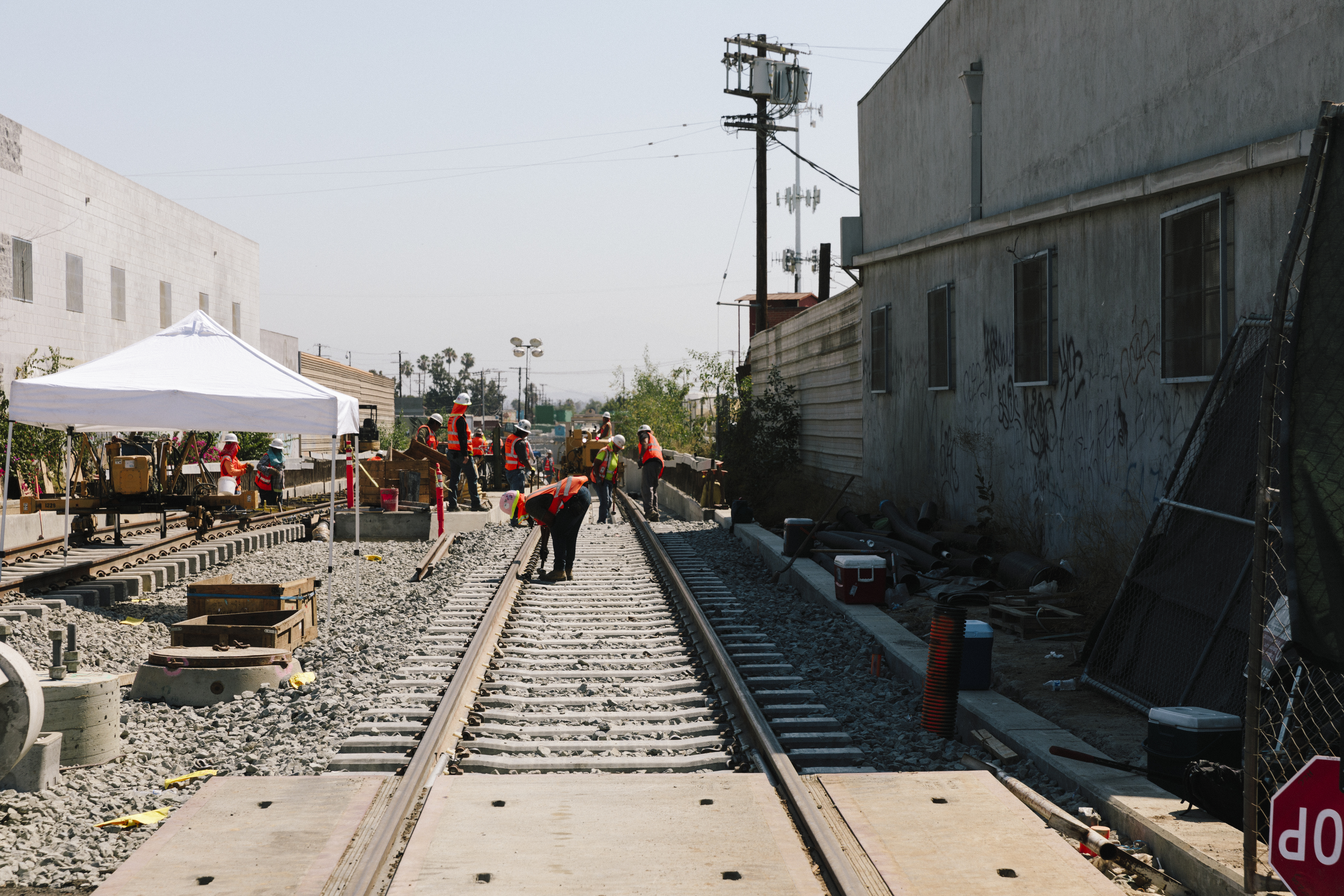 Workers gathered around train tracks, with construction equipment in the area