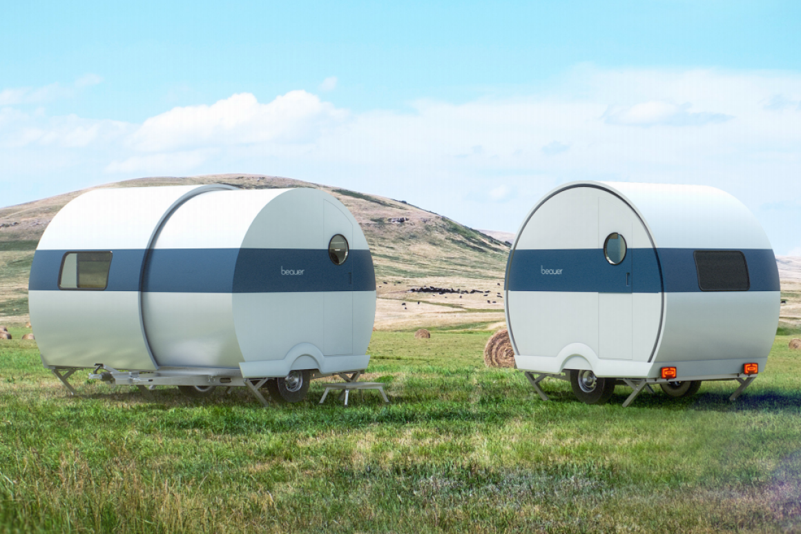 Two silver, semi-circle camper trailers sit in a field of grass. On the left the camper is expanded while on the right the camper is smaller.
