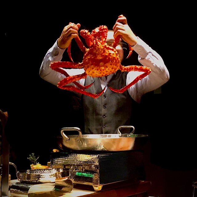 A chef holds up a king crab by the claws over a metal pan.