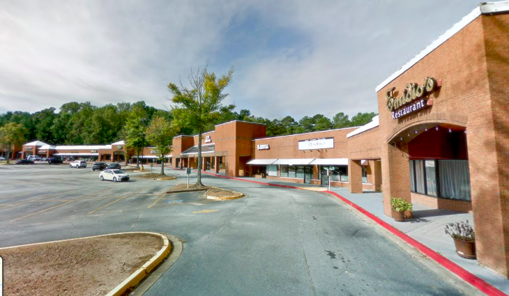 A strip mall made of brick with acres of surface parking lots at left.